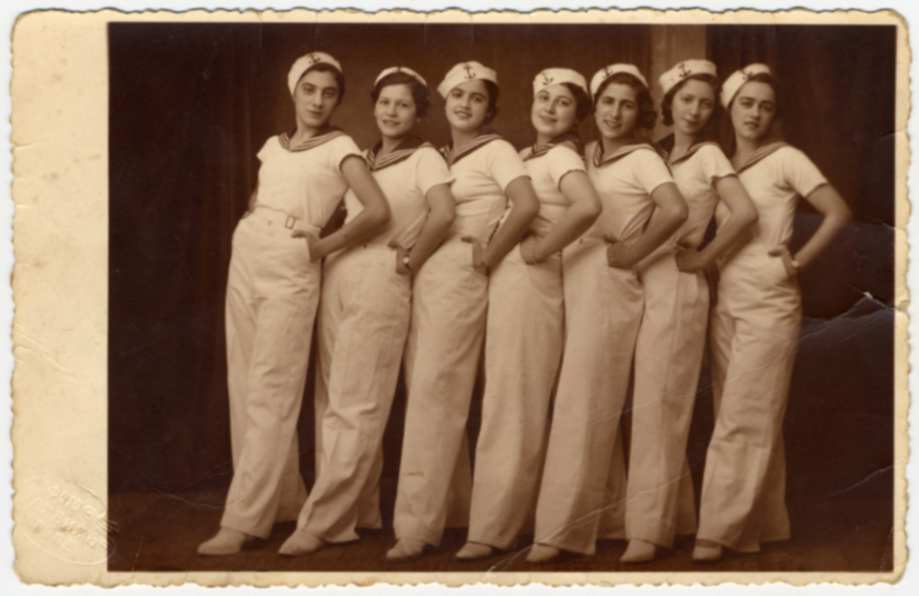 A Maccabi gymnastic team poses standing in a row in sailor costumes.  Victoria Ashkenazi is pictured third from the left.