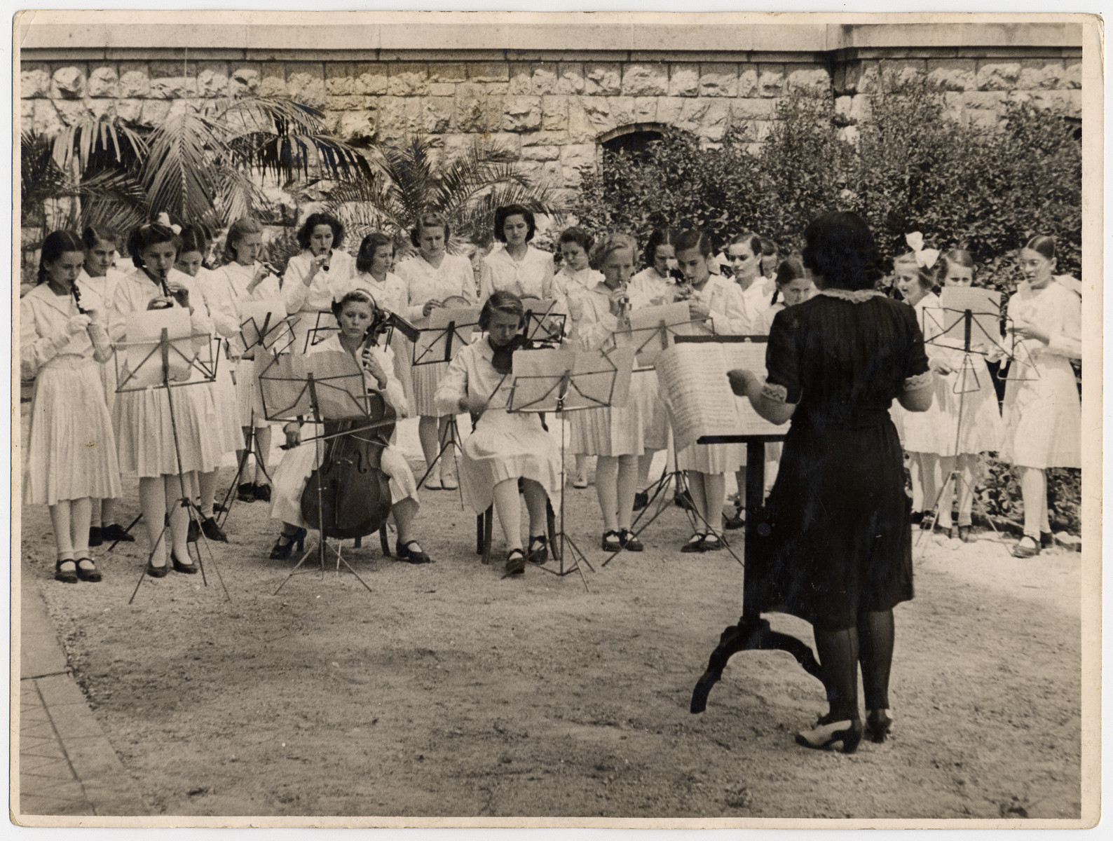 A Jewish born woman in hiding conducts a school orchestra in a Catholic school near Budapest.  Pictured is Ella Lichtag Schichtanz (the conductor).