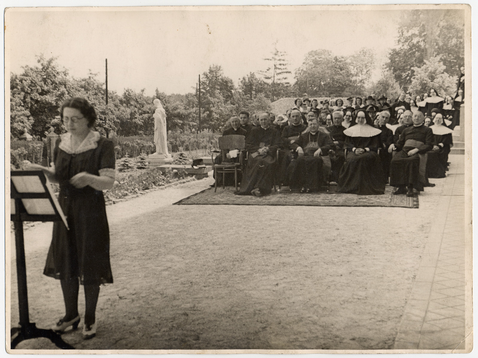 A Jewish born woman in hiding conducts a school orchestra in a Catholic school near Budapest.  Pictured are Ella Lichtag Schichtanz (the conductor) and the Mother Superior, Mater Krigovzky, and the Hungarian Archibishop in the audience.