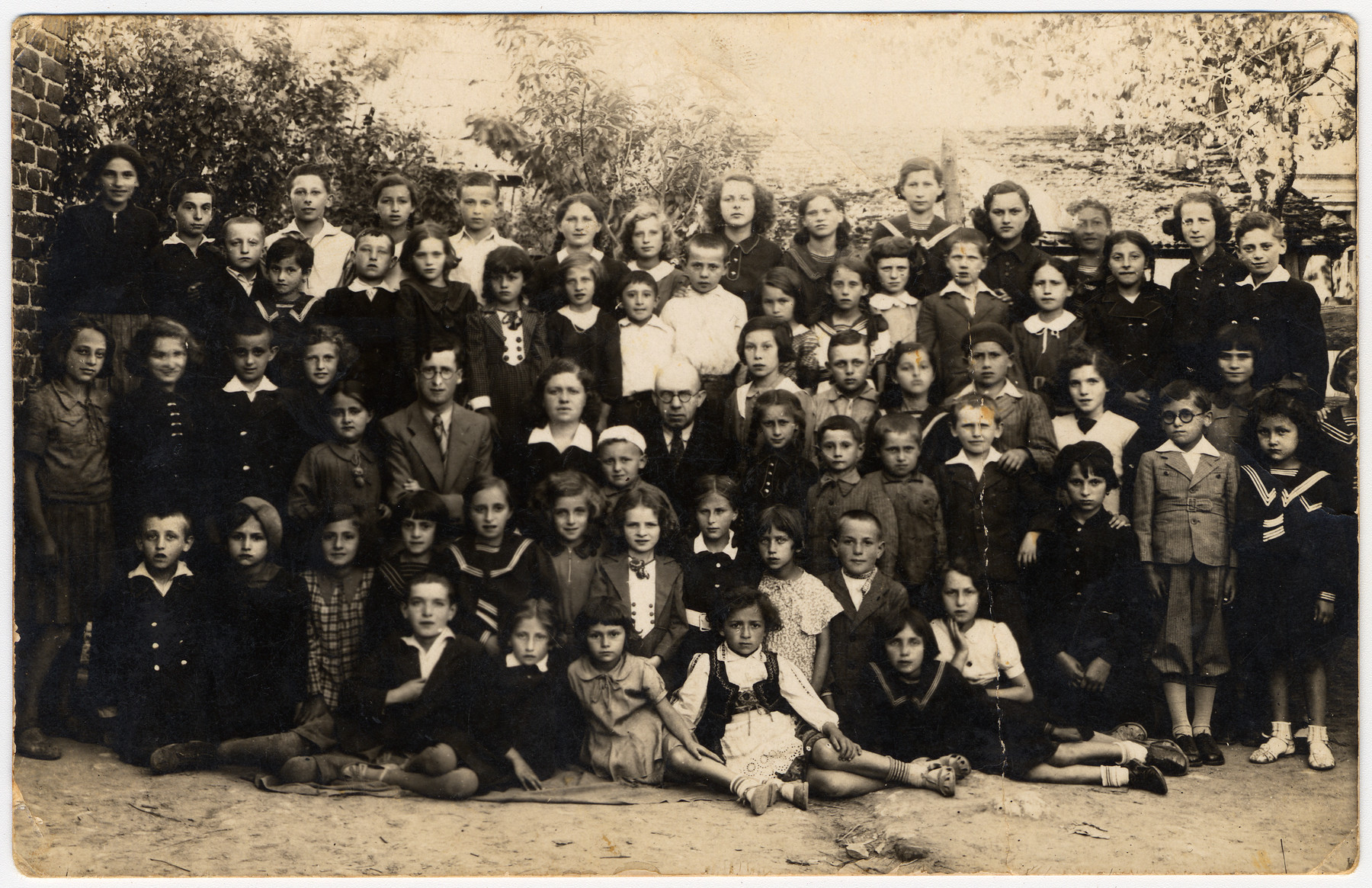 Group portrait of the children and teachers in the Tarbut school in Belzyce.  Sara Wiener is pictured in the third row, fourth from the left.  Her sister Dina is pictured in the second row, sixth from the left.  The fourth person from the left, top row is Esther Lajwand,  The second person from the left, fourth row is Ethel Lajwand, sister to Esther.   In the fourth row, fourth from the right (wearing a beret) is Kalman (Carl) Lajwand, brother to Esther and Ethel.