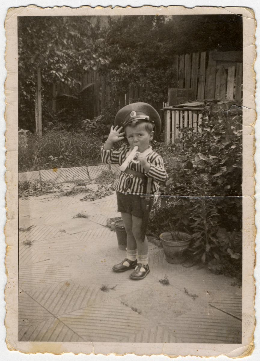 A young Jewish boy, Misha Avramoff, plays a toy trumpet while wearing a  Bulgarian officer's hat in Ruse, Bulgaria.