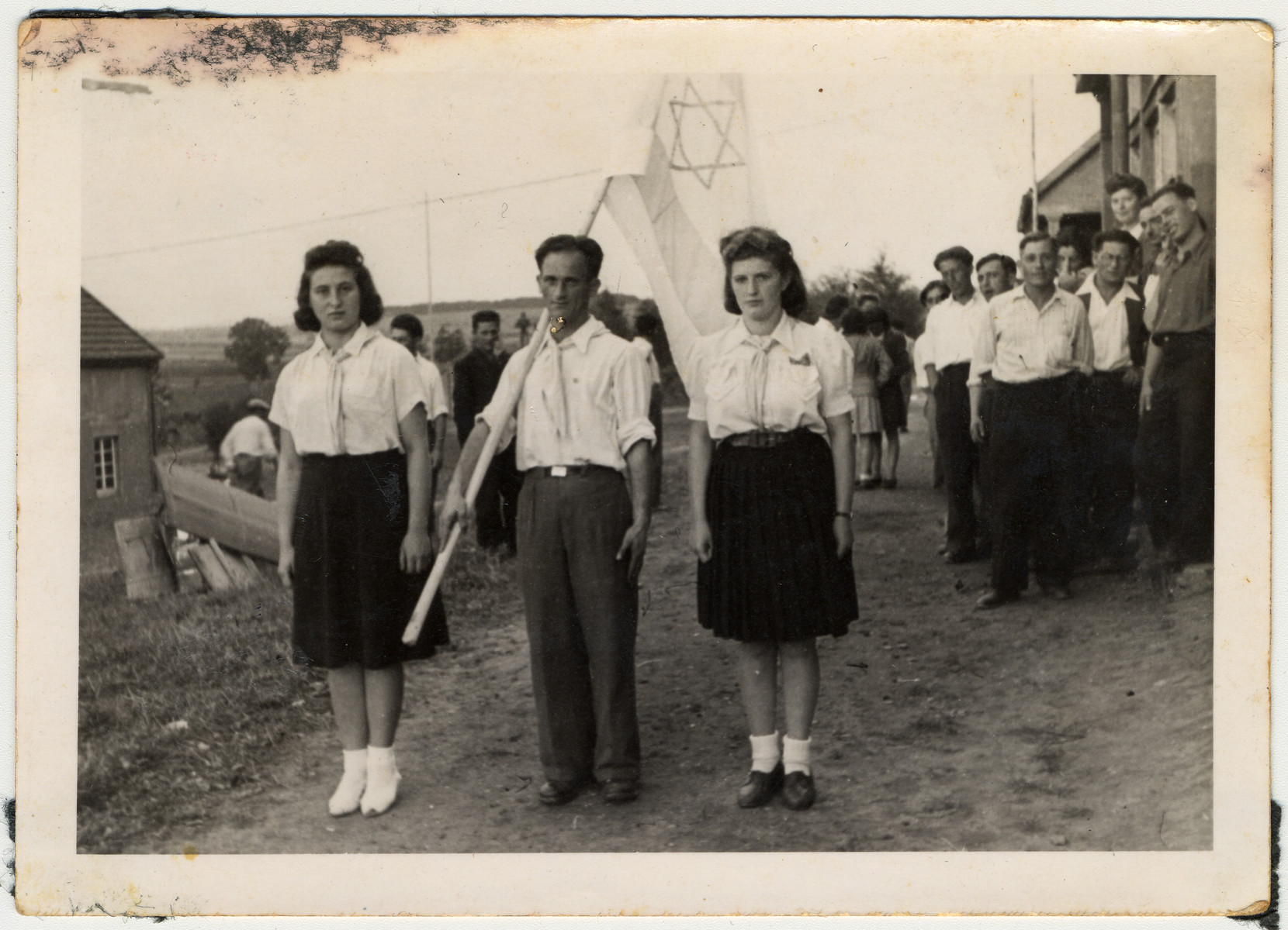 Jewish displaced persons stand at attention with a flag during a Zionist demonstration in Kibbutz LaNegev.  Pictured in the foreground on the right is Sara Wiener.
