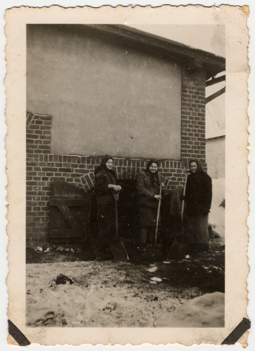 Three women forced laborers in Dabrowka hold shovels while standing in front of a building.   Pictured are from the left to the right: unknown, Rika Czerniak and Ruth Anzer.