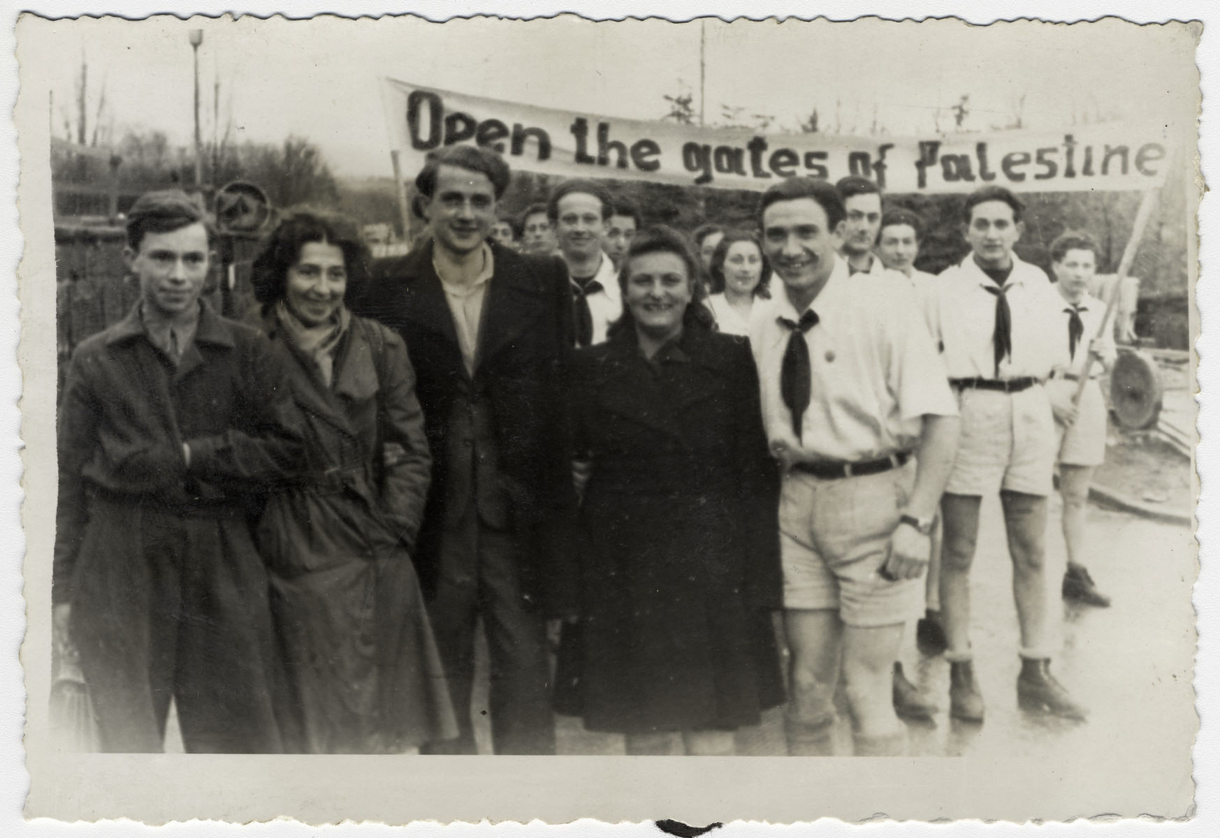 "Members of Kibbutz Havivah Reik demonstrate against British Palestine immigration policy.  In the background is a banner that says, ""Open the gates of Palestine.""  Willy Bogler is standing in the center."