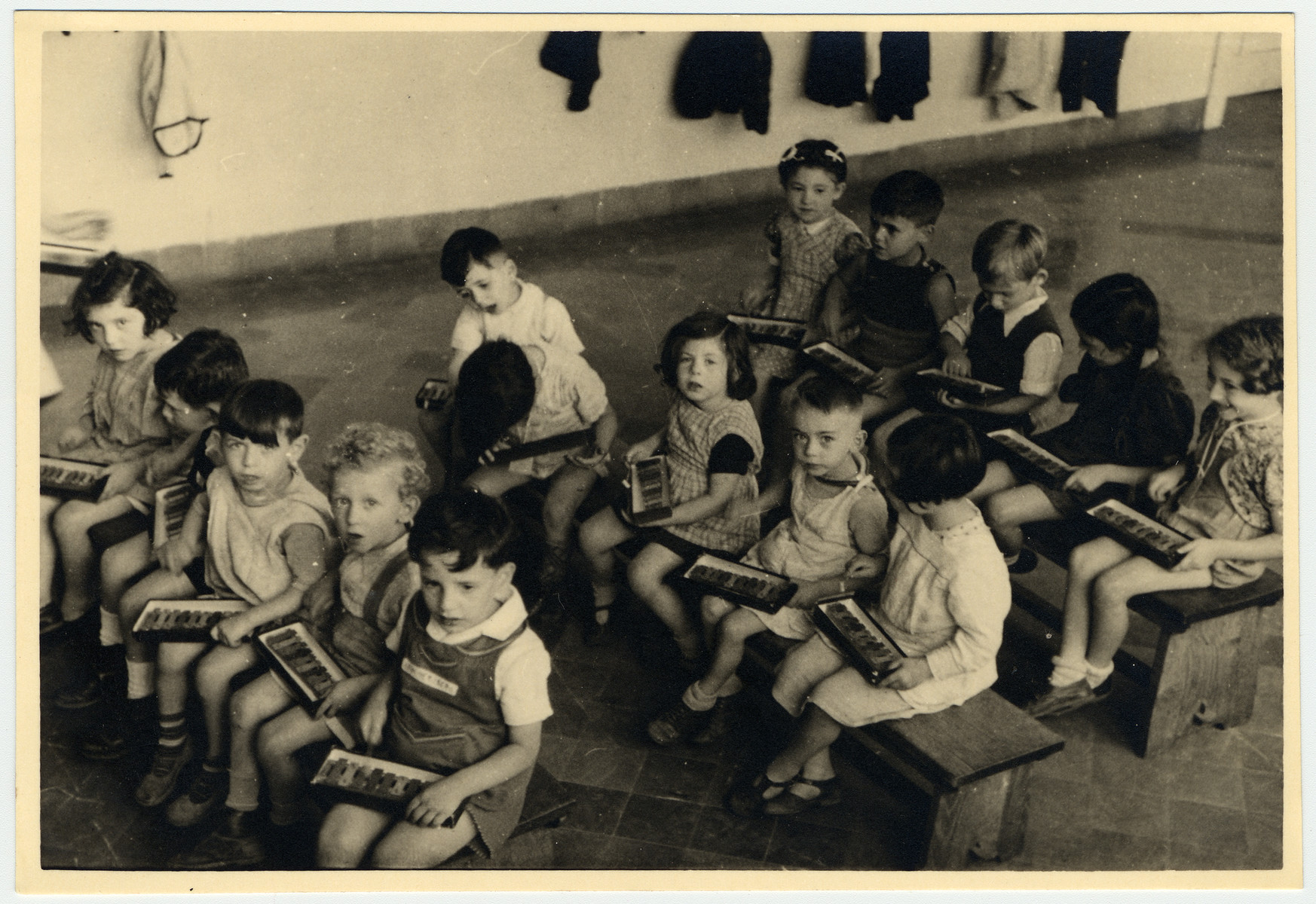 Children in the Nos Petits Jewish kindergarten sit in a classroom holding small xylophones.