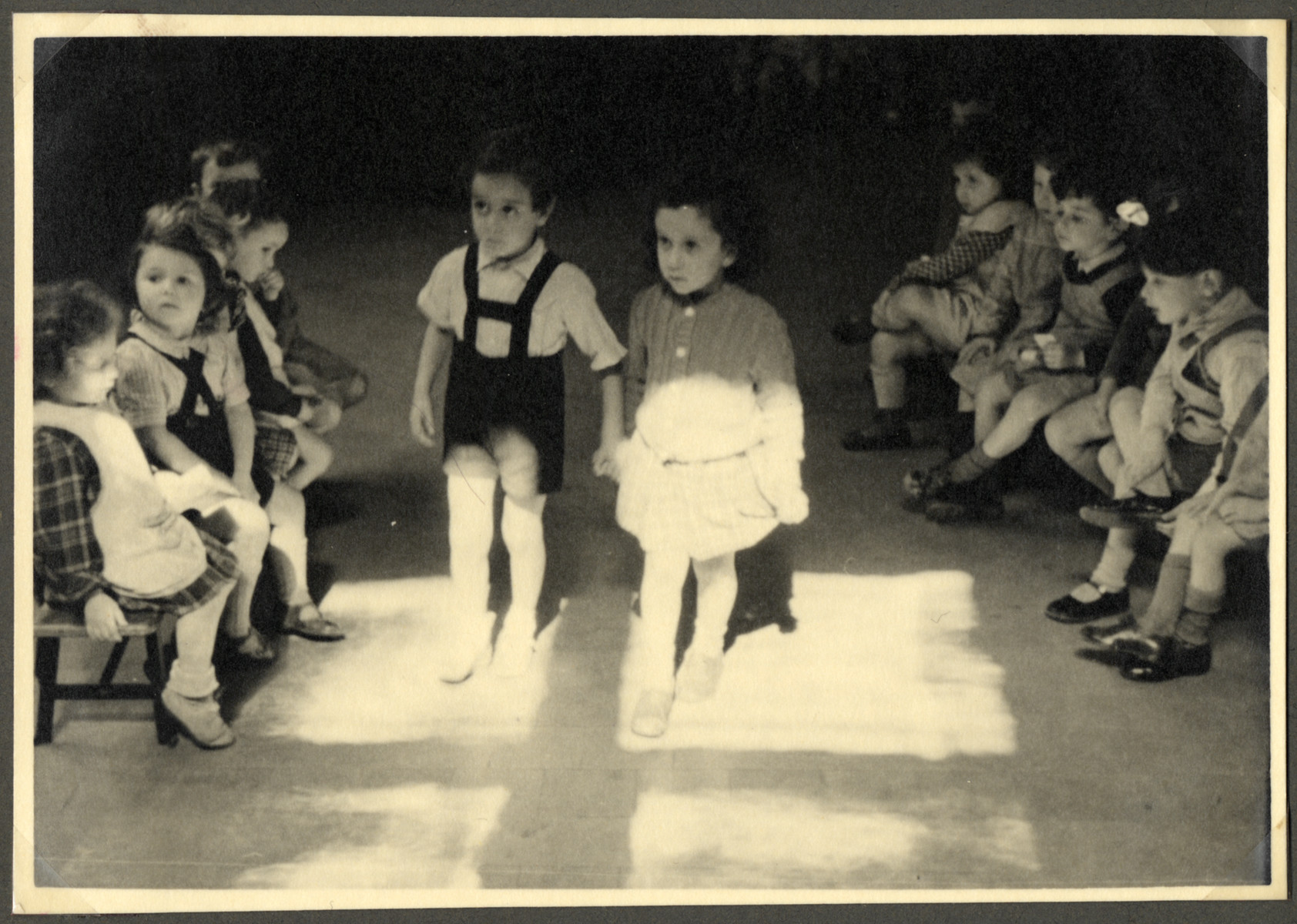 Two children walk hand-in-hand in a classroom in the Nos Petits Jewish kindergarten while other children watch on either side.