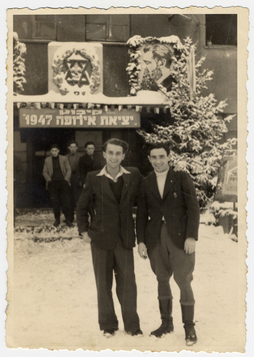 "Willy Bogler (left) and Saul Zohar (right) pose in front of the entrance of a building with a large sign ""Exodus 1947."""