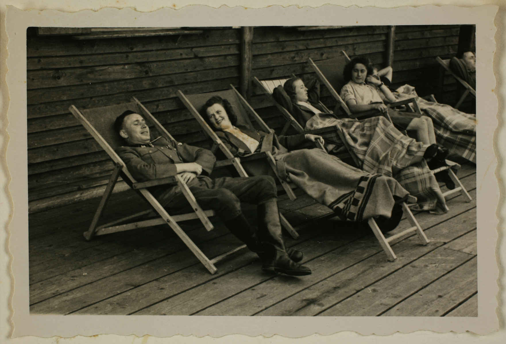 "SS officer Karl Hoecker relaxes with women in lounge chairs on the deck of the retreat in Solahuette.  The original caption reads ""On the terrace of the lodge""."
