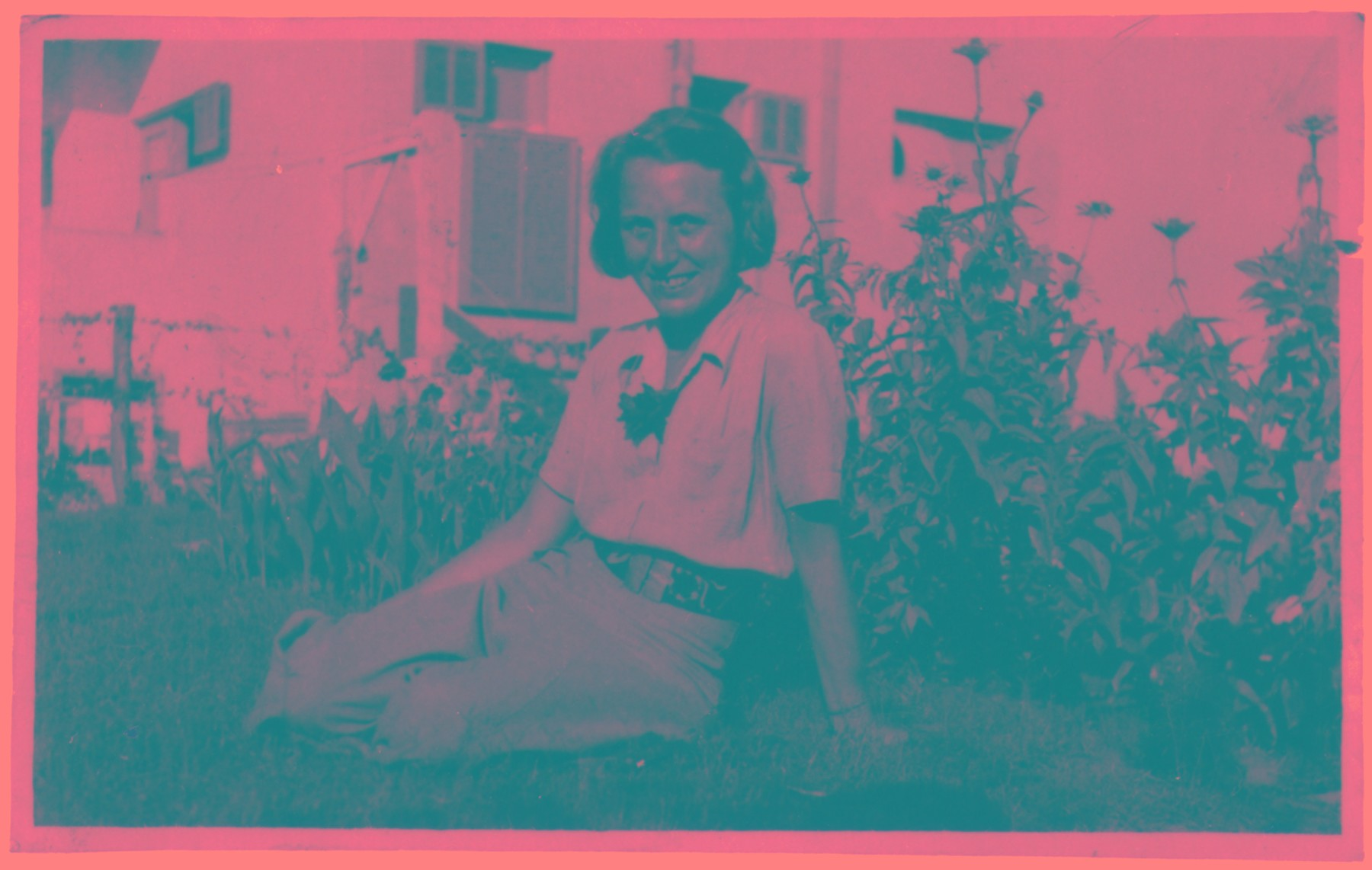 Portrait of Isabella Wiener Ronen seated on the lawn in front of a flower bed.