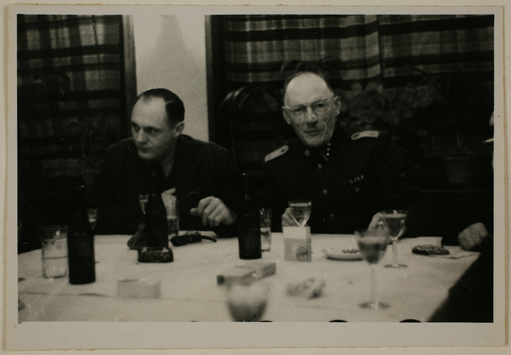 Two SS officers gather for drinks in a hunting lodge.  On the right is Heinrich Josten, and on the left is Eduard Wirths.