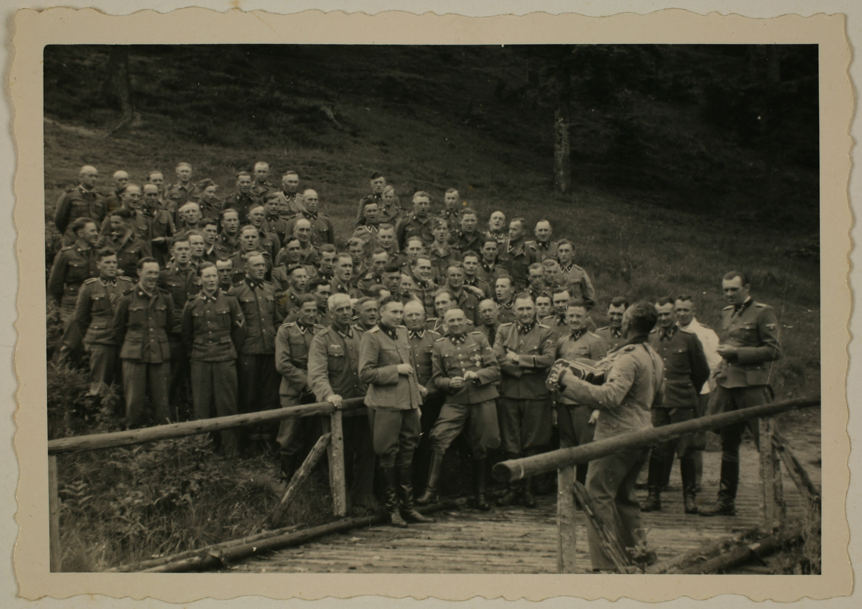 An accordionist leads a sing-along for SS officers at their retreat at Solahuette outside Auschwitz.  Pictured in the front row are Karl Hoecker, Otto Moll, Rudolf Hoess, Richard Baer, Josef Kramer (standing slightly behind Hoessler and partially obscured), Franz Hoessler, Josef Mengele, and Walter Schmidetzki.  Hermann Buch is in the center.  Konrad Wiegand, head of the Fahrbereitschaft (car and truck pool) is in the middle.  [Based on the officers visiting Solahutte, we surmise that the photographs were taken to honor Rudolf Hoess who completed his tenure as garrison senior on July 29.]