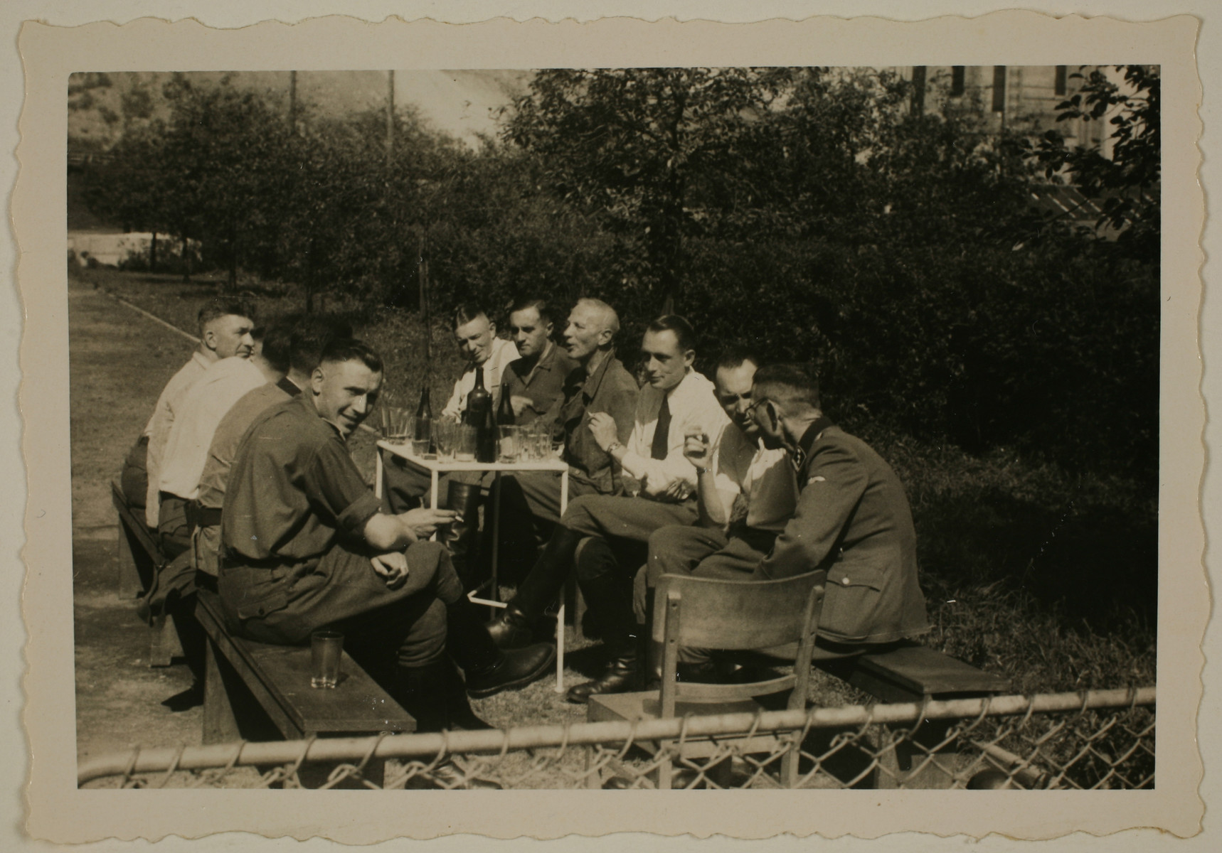 "SS officers, including several SS physicians, sit around a table drinking probably following a visit to coal mine.    The original caption reads ""Nach der Ausfahrt"" (after the outing).  Among those pictured are Karl Hoecker (far left), Dr. Fritz Klein (left hand side, end of table), Dr. Horst Schumann, Gerhard Gerber, Dr. Eduard Wirths (right side of the bench, third from the front) and Dr. Willi Schatz (right side, end)."