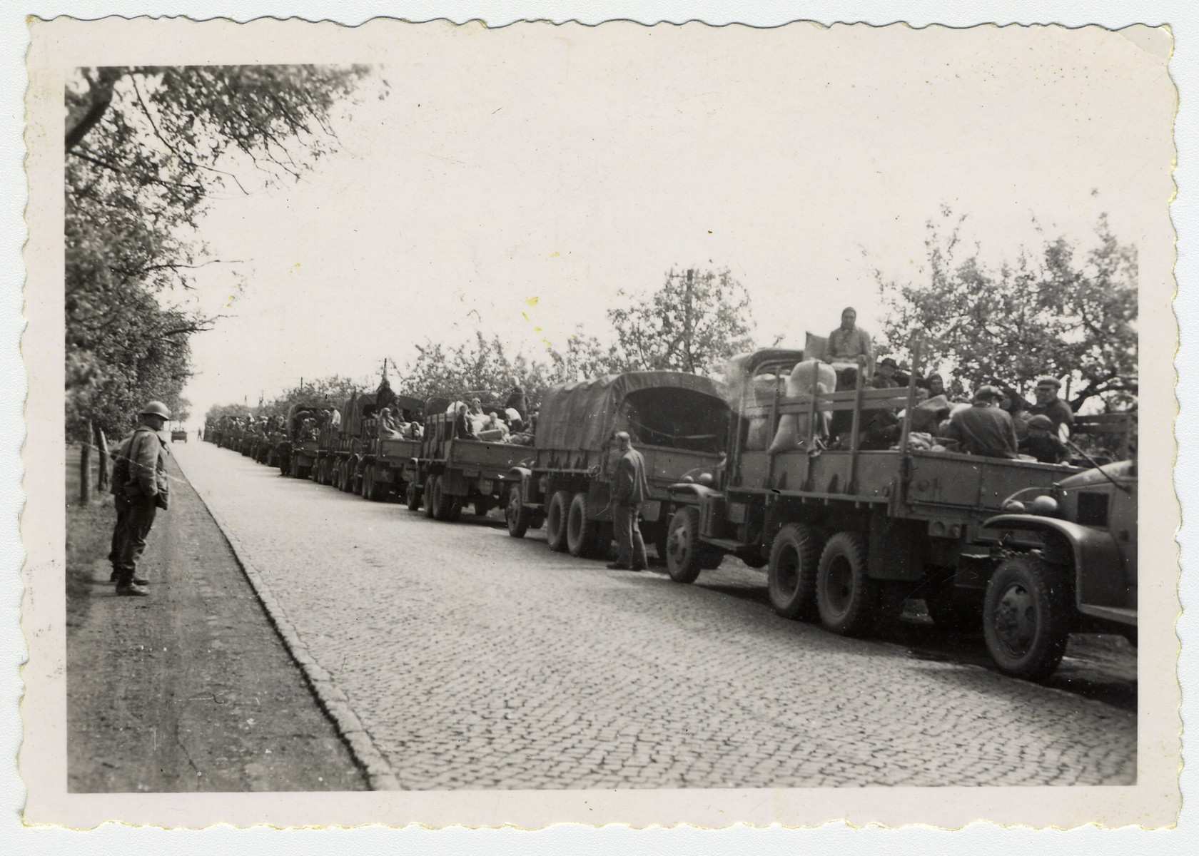 Displaced persons en board a truck convoy prepare to emigrate, assisted by members of the U.S. Army.