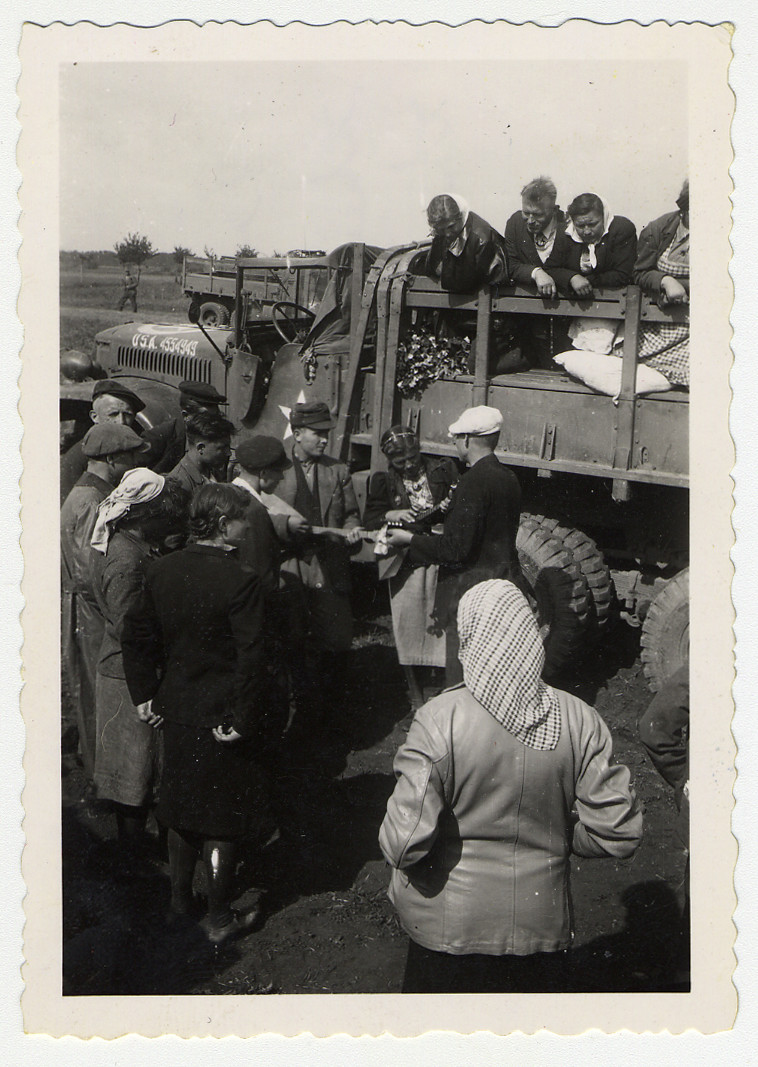Displaced persons prepare to emigrate, assisted by members of the U.S. Army.  Original caption reads: Loading DPs. One of their number checks them off.