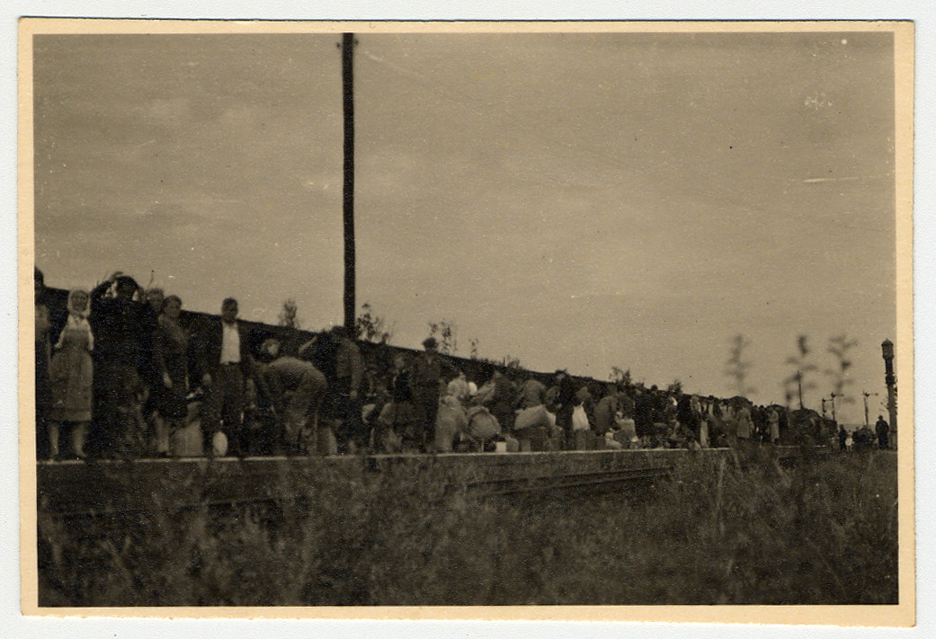 Displaced persons stand on the train platform.  Original Caption reads: DPs detrained on the platform.