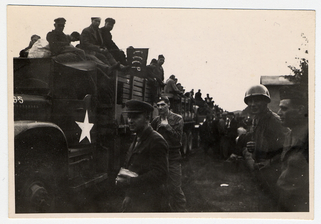 Displaced persons prepare to emigrate, assisted by members of the U.S. Army.  Original caption reads: Russian Major supressing boarding of DPs.