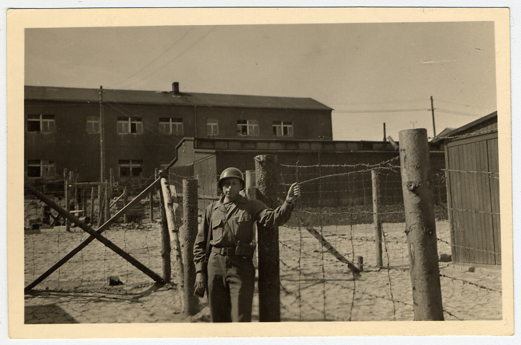 An American soldier poses in front of a fence in Buchenwald concentration camp.