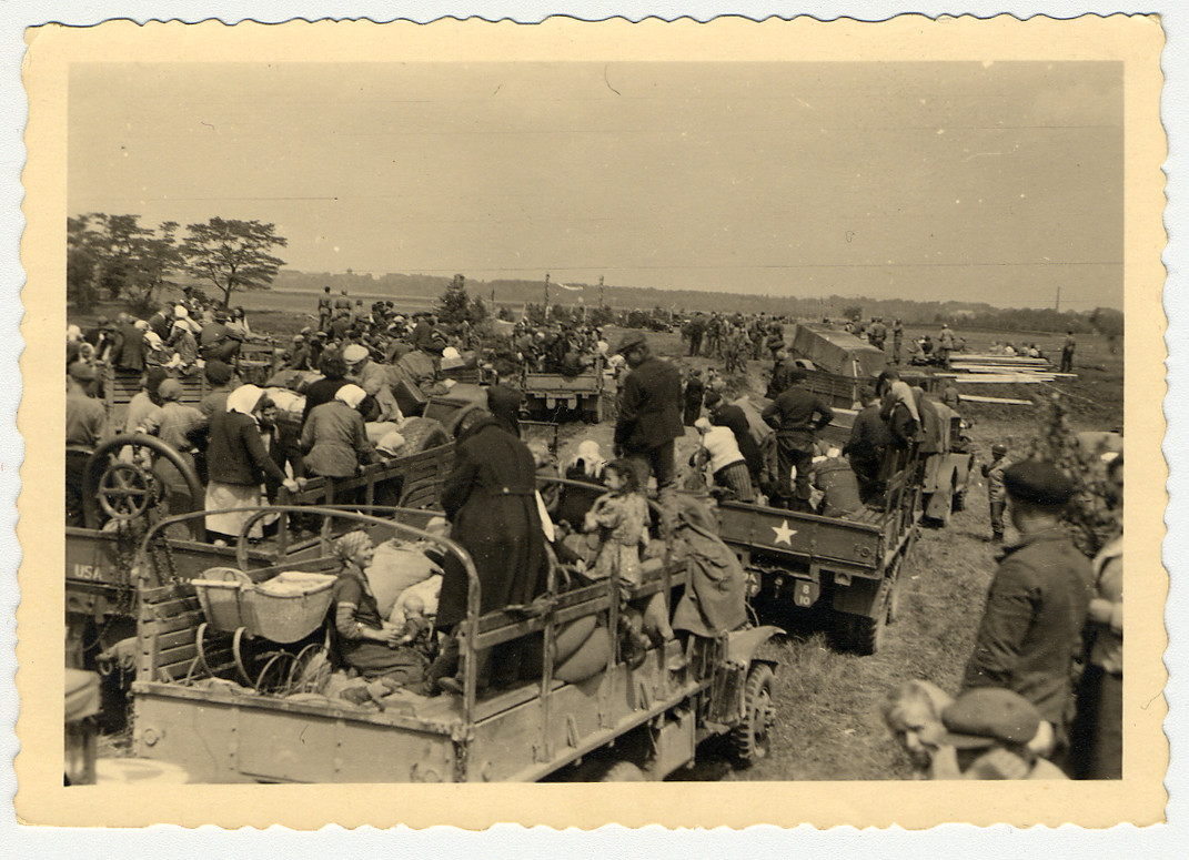 Displaced persons prepare to emigrate, assisted by members of the U.S. Army.