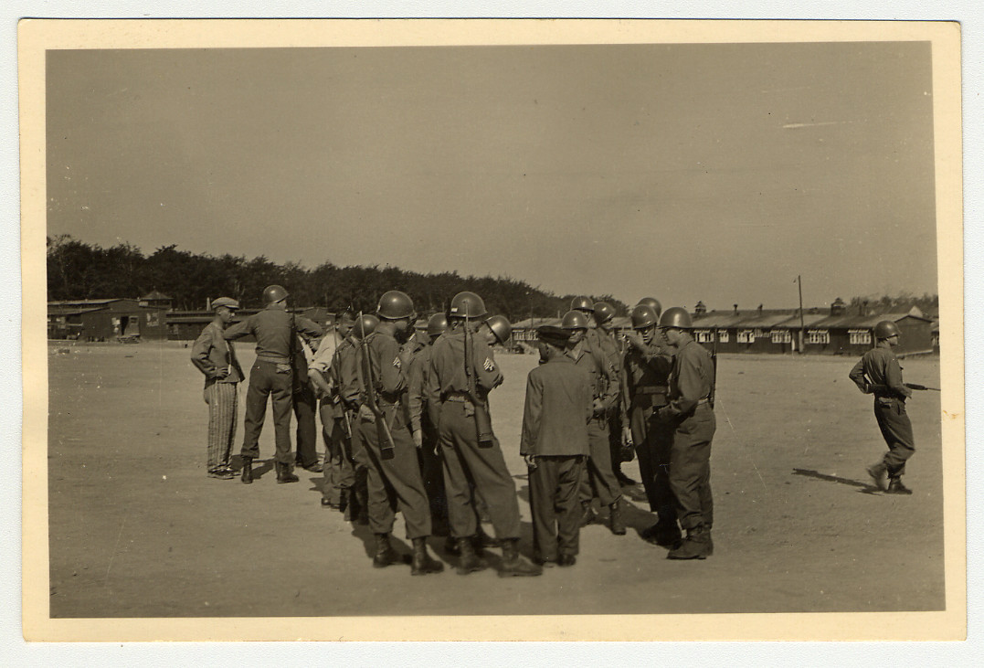 A group of liberating U.S. Army soldiers speak with prisoners in the Buchenwald concentration camp.  Original Caption reads: As we entered the camp former inmates approached us, telling us about the place and offering to serve as guides. Here the men listen intently, part of camp in background.
