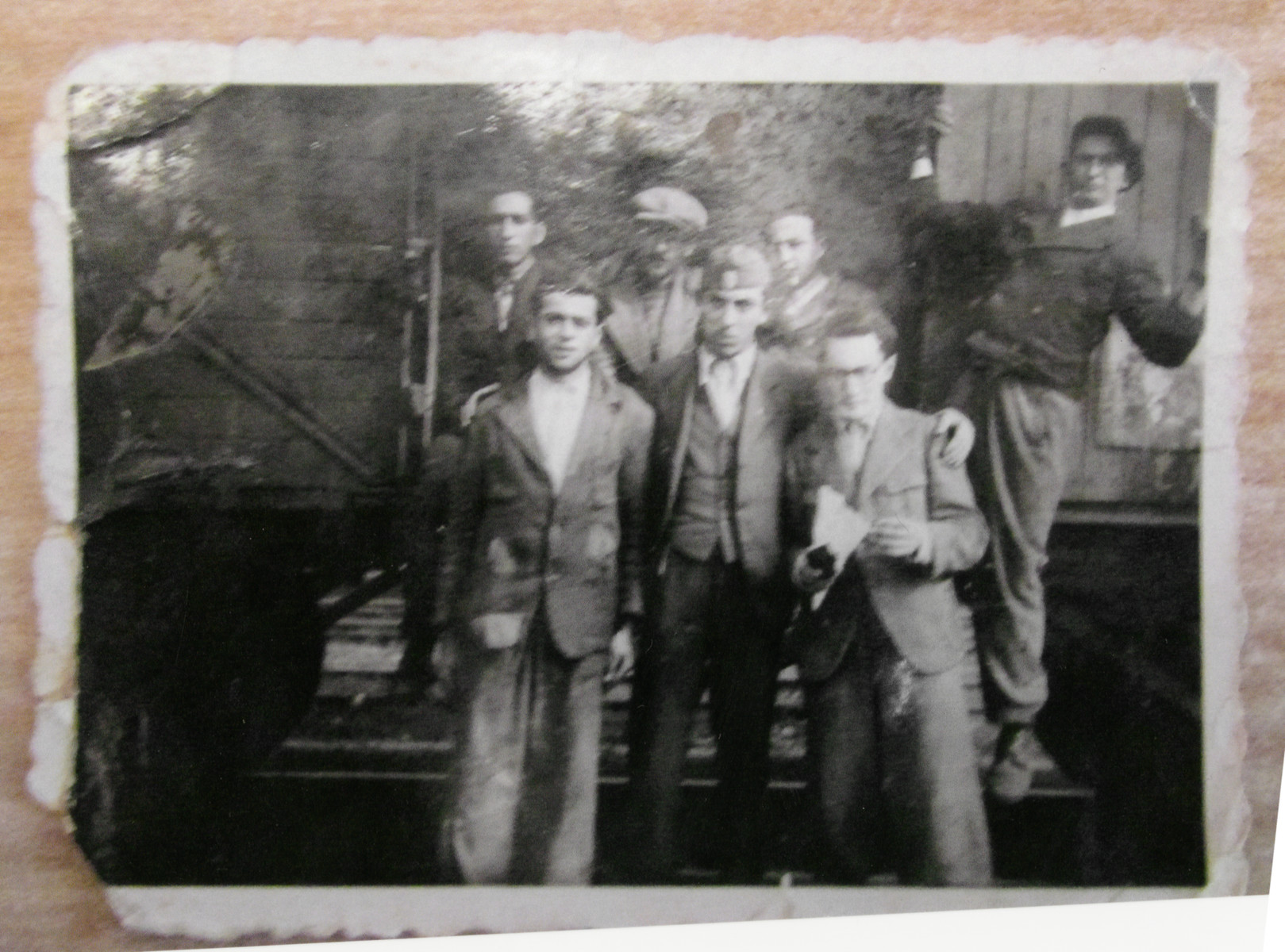 Young Jewish Hungarian men gather by a train during their service in a forced labor battalion.  Among those pictured is Karoly Jakubovitz in the front row, center (with the cap).