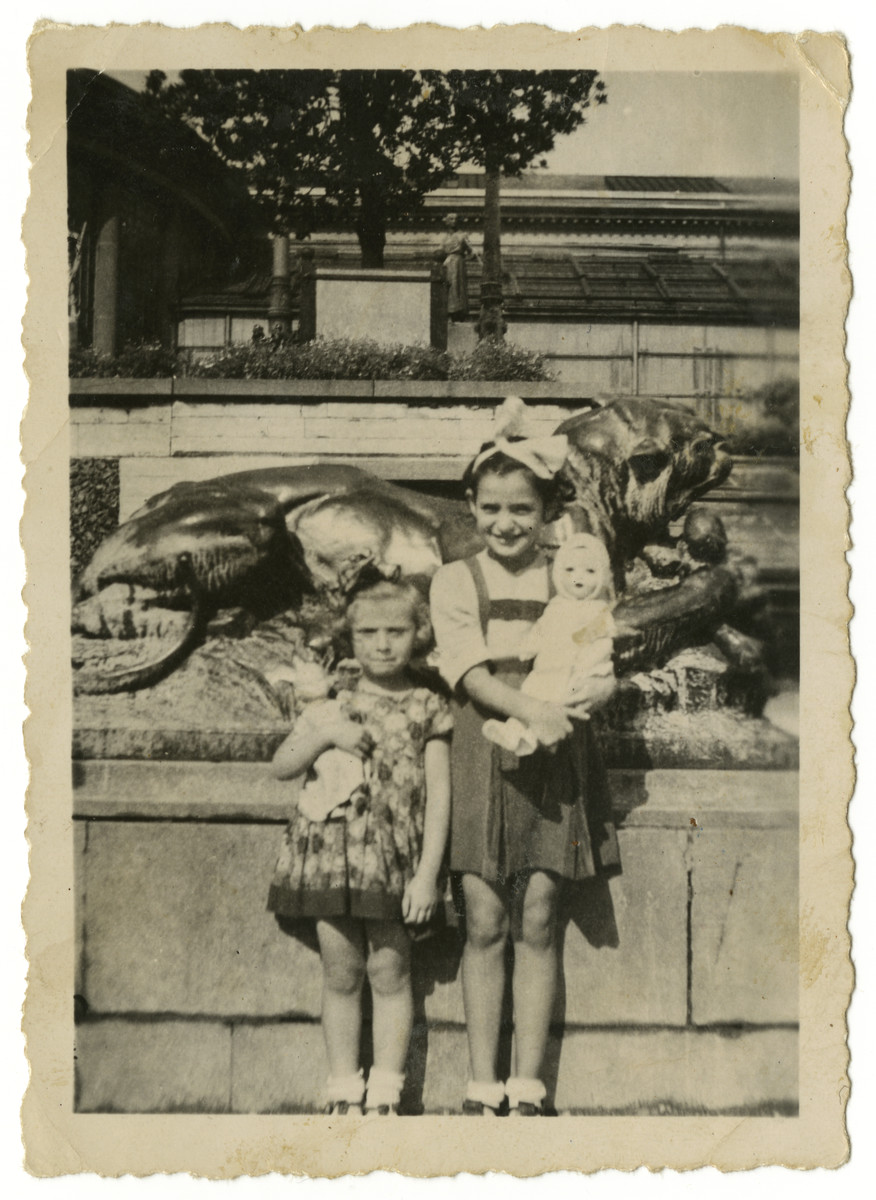 Renee Schwalb and a younger friend stand holding their dolls nex to a statue.