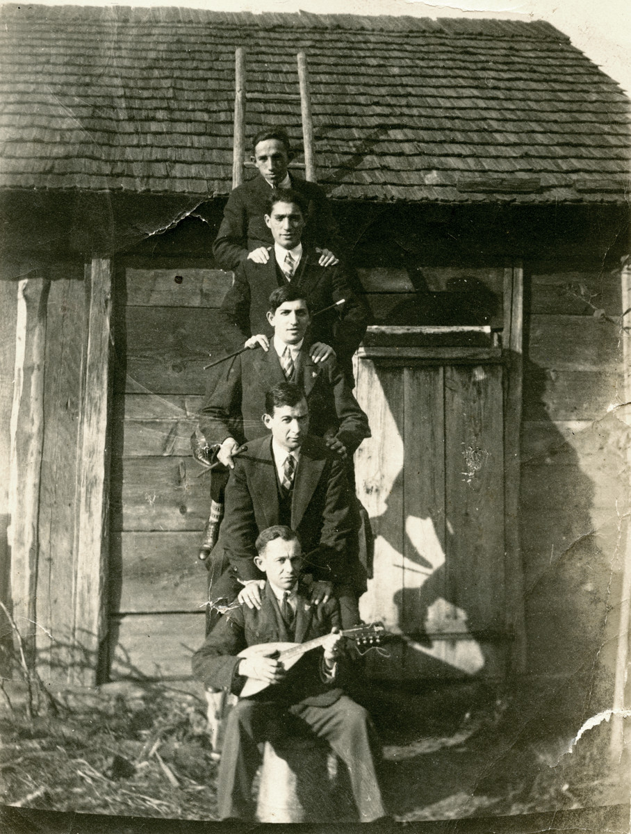 Five young male students posie on the rungs of a ladder outside of a building that looks like a barn or shed.   Feivel Frankfowicz is pictured on the bottom of the ladder holding a mandolin
