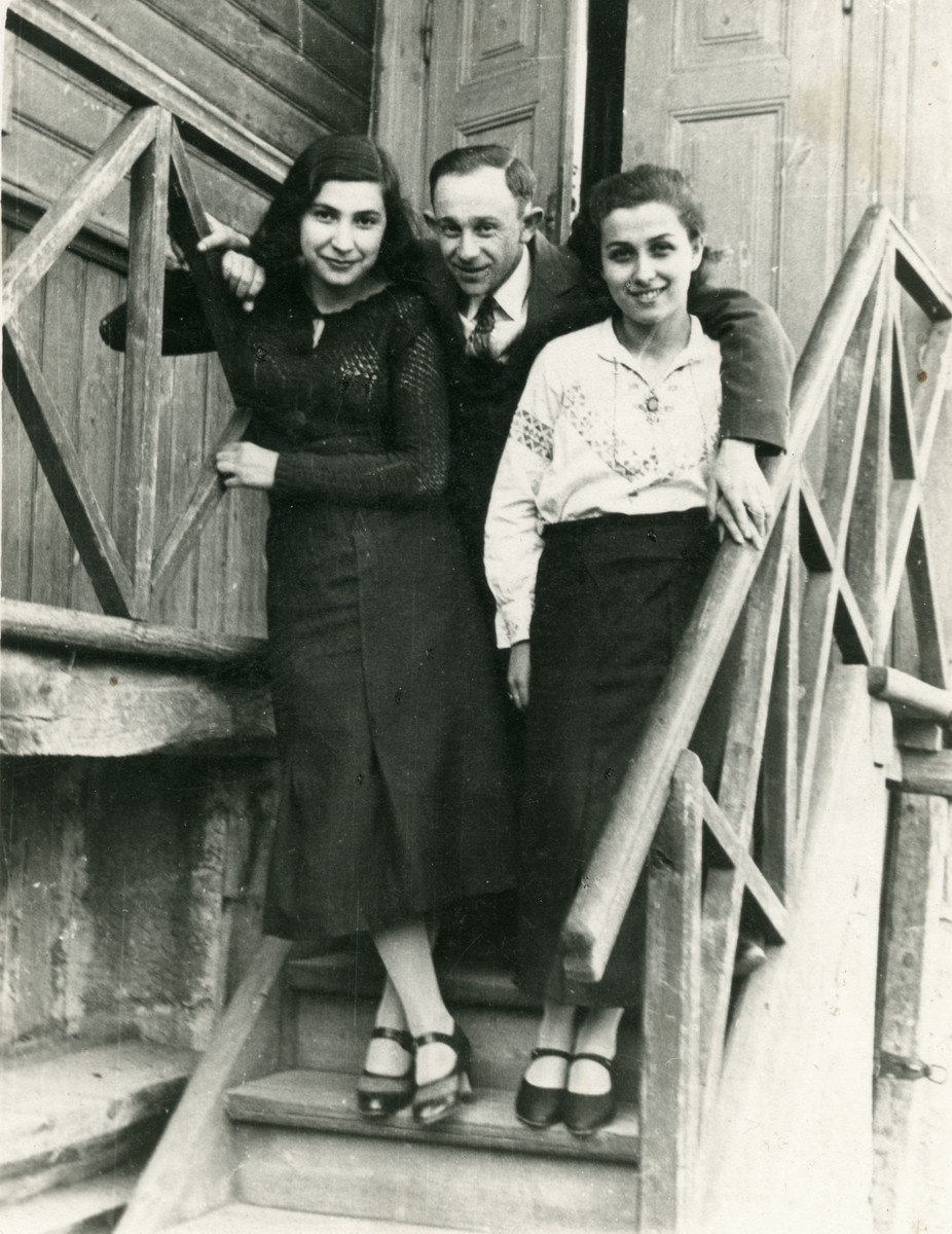 A photo of two women and one man standing on the staircase of a building.   From left to right Chana Frankfowicz (who later perished in the Holocaust), her brother Feivel Frankfowicz, and his future wife Ethel Rytt.