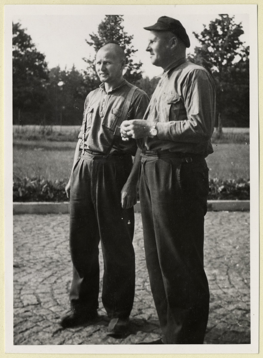 Portrait of two former political prisoners standing on the grounds of the Dachau concentration camp, shortly after liberation.