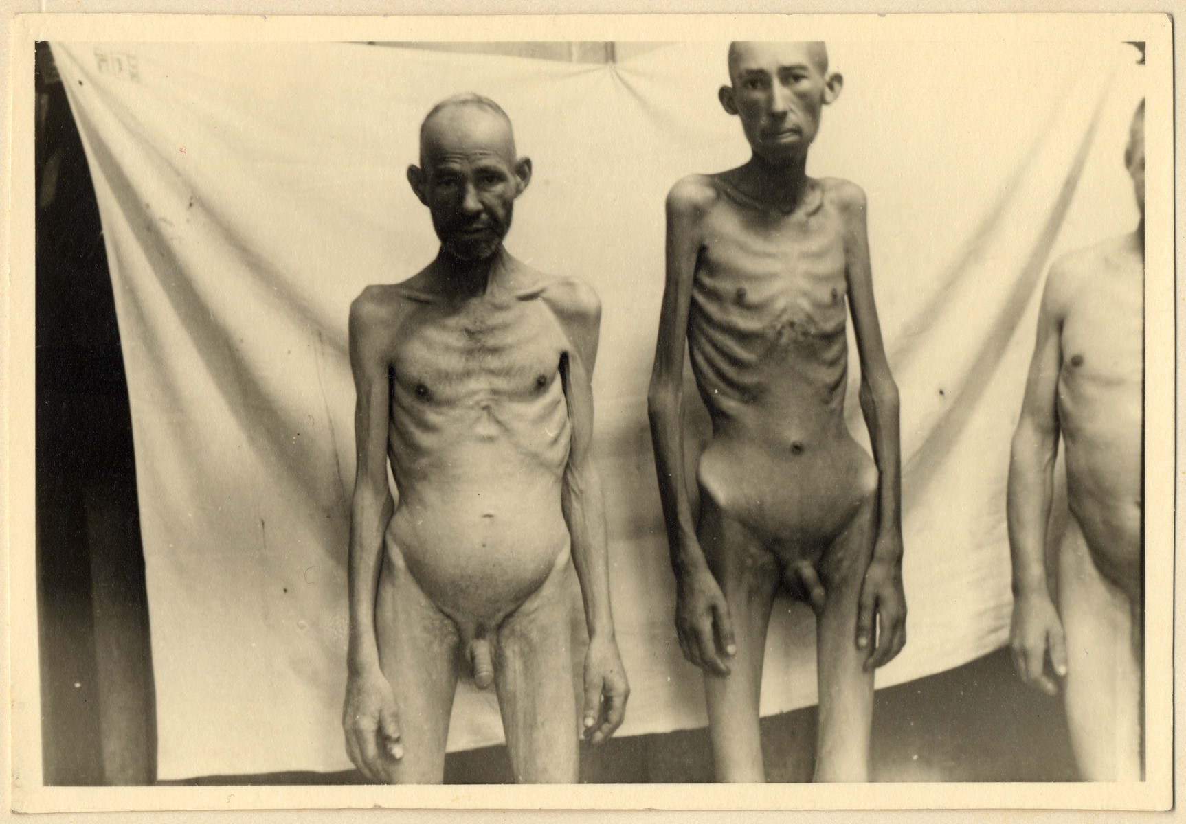 Close-up photograph of two naked, starving prisoners in the Dachau concentration camp.  This photograph was taken to the photo lab where Maria Seidenberger worked.  She developed the photo, kept a copy and shared it with Karel Kasak, a Czech political prisoner.