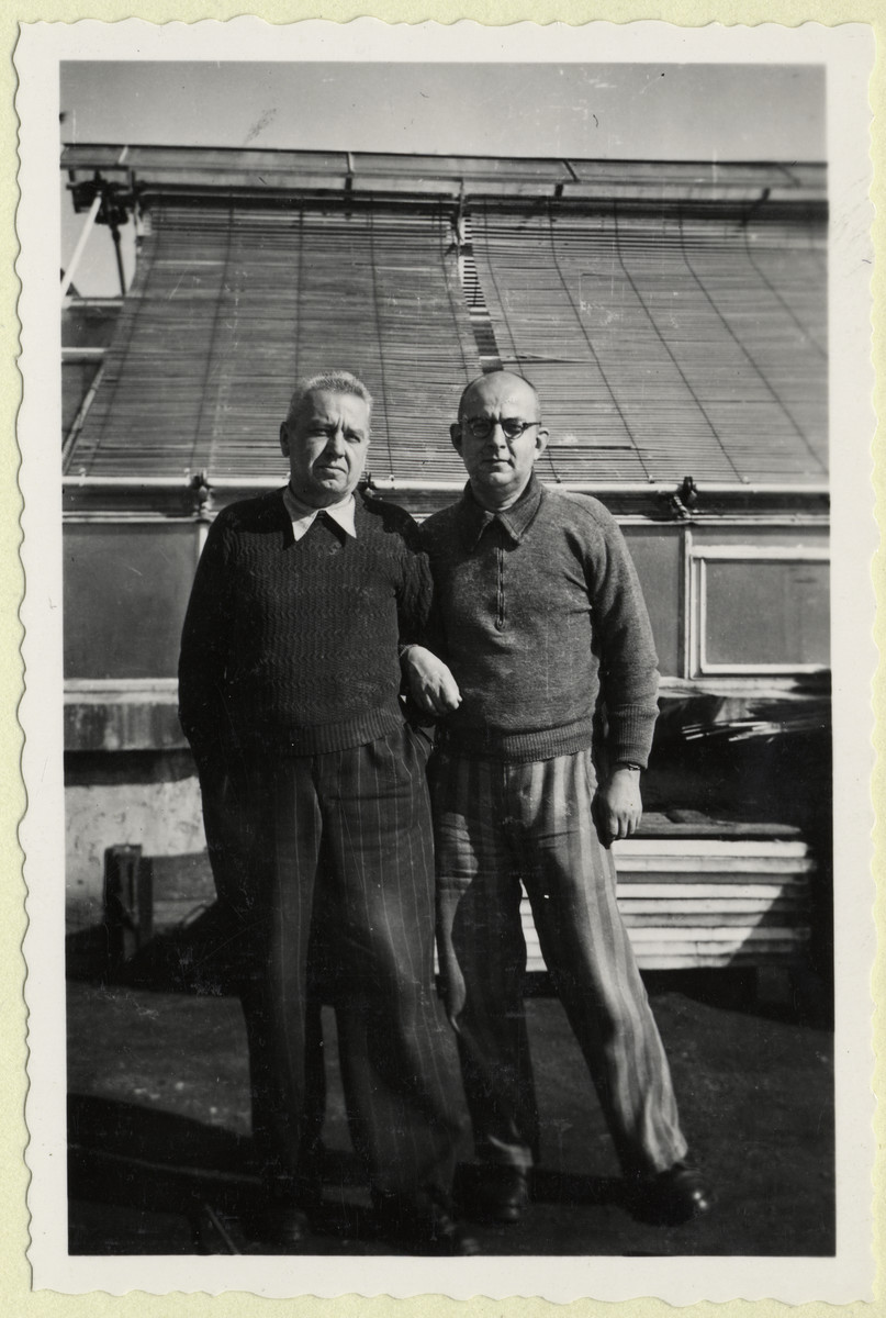 Two Czech political prisoners stand next to the greenhouse in the Dachau concentration camp.  The photograph was taken by Karel Kasak and developed by Maria Seidenberger.