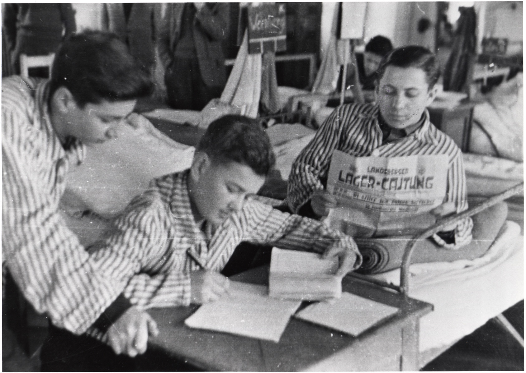 Young patients in the Landsberg DP camp hospital read the camp newspaper and write at a desk.