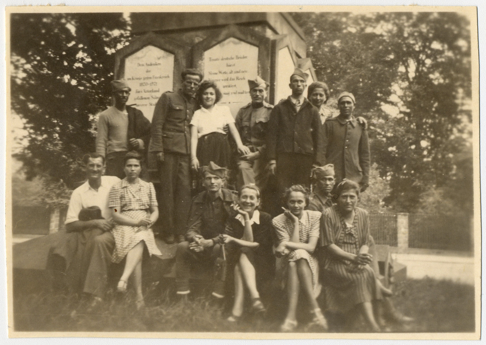 Group portrait of displaced persons and Soviet soldiers standing in front of a memorial shortly after liberation.  Livia Vermes is pictured in the front row, second from the right.