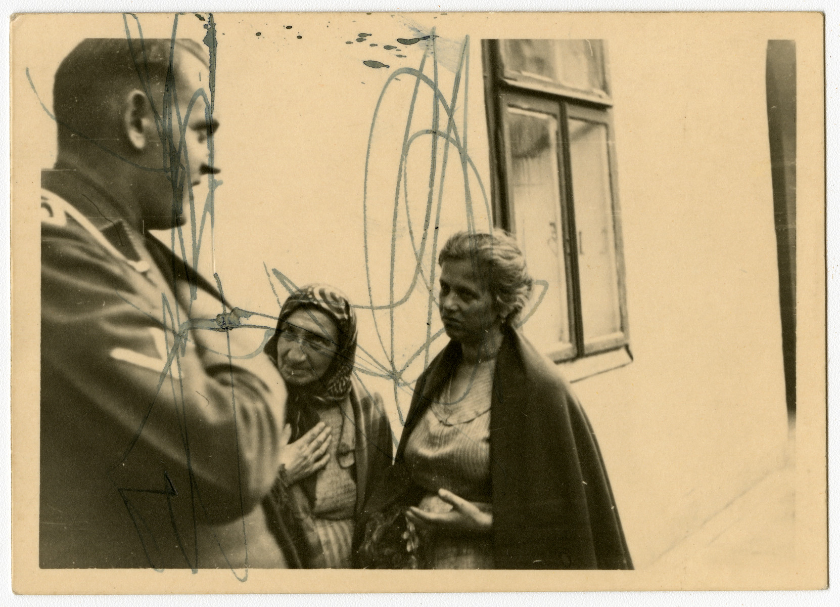 An SD officer questions two women before an unidentified exterior.  This image is one of twenty-six contained in an album found by Jacob Igra in an apartment in Sosnowiec after the war. Many of the photographs are believed to have been taken by a soldier with the SD-SIPO (Sicherheitspolizei) following the invasion of Poland in 1939. Additional photographs depict einsatzgruppen activities at sites throughout Nazi occupied Eastern Europe and may have been later additions to the album.