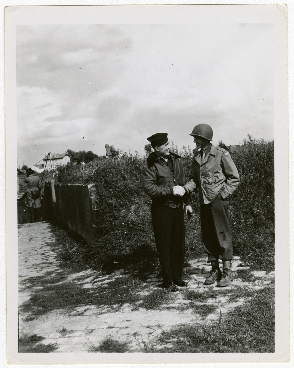 "Fred Astaire shakes hands with a US soldier during his goodwill visit to France.  The original caption reads ""Fred Astaire visits Normandy. Astaire is on the right."""