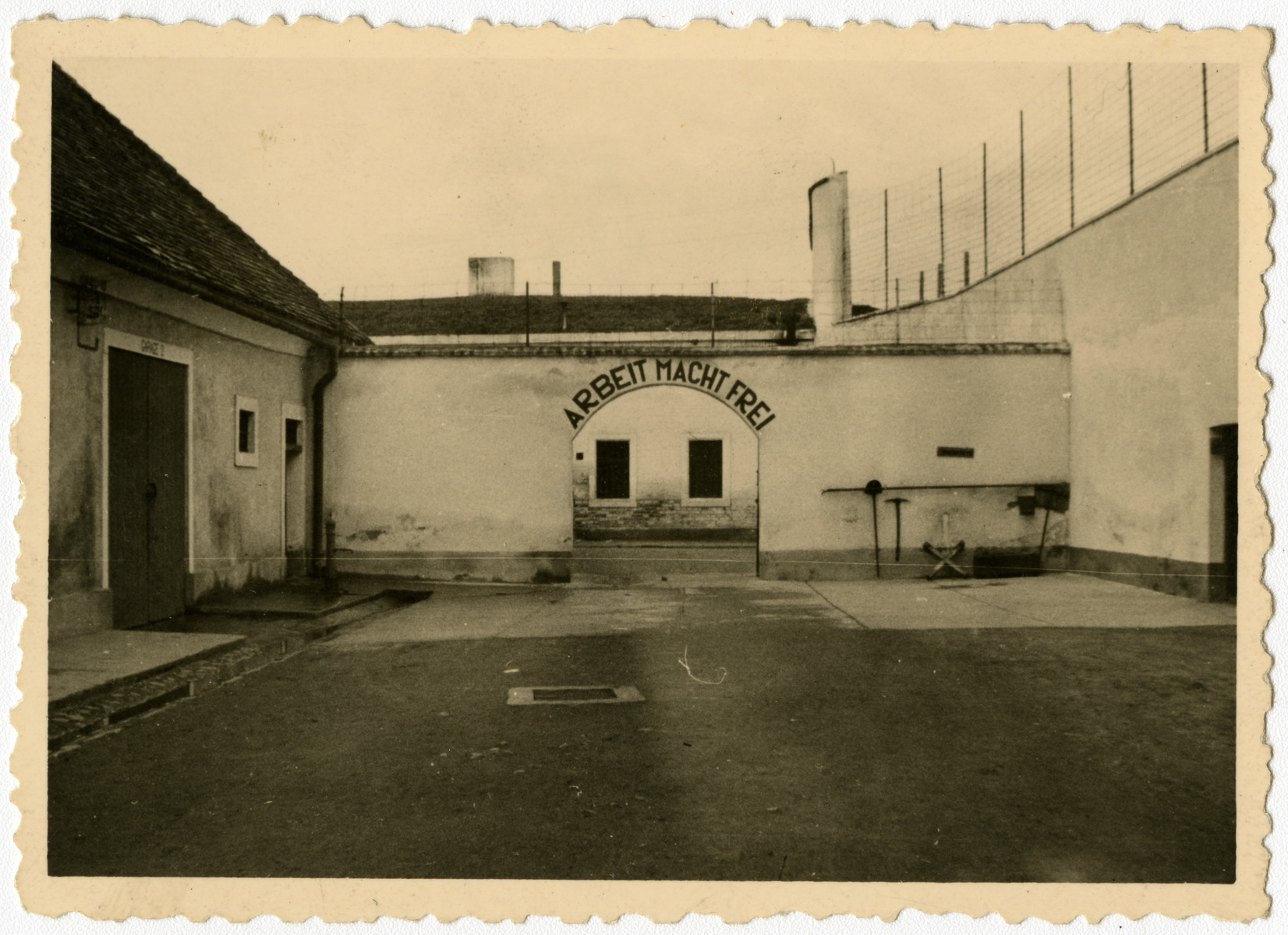 "An archway at Theresienstadt bearing the phrase, ""Arbeit Macht Frei.""   This image is one of twenty-six photographs contained in an album found by Jacob Igra in an apartment in Sosnowiec after the war. Many of the photographs are believed to have been taken by a soldier with the SD-SIPO (Sicherheitspolizei) following the invasion of Poland in 1939. Additional photographs depict einsatzgruppen activities at sites throughout Nazi occupied Eastern Europe and may have been later additions to the album."
