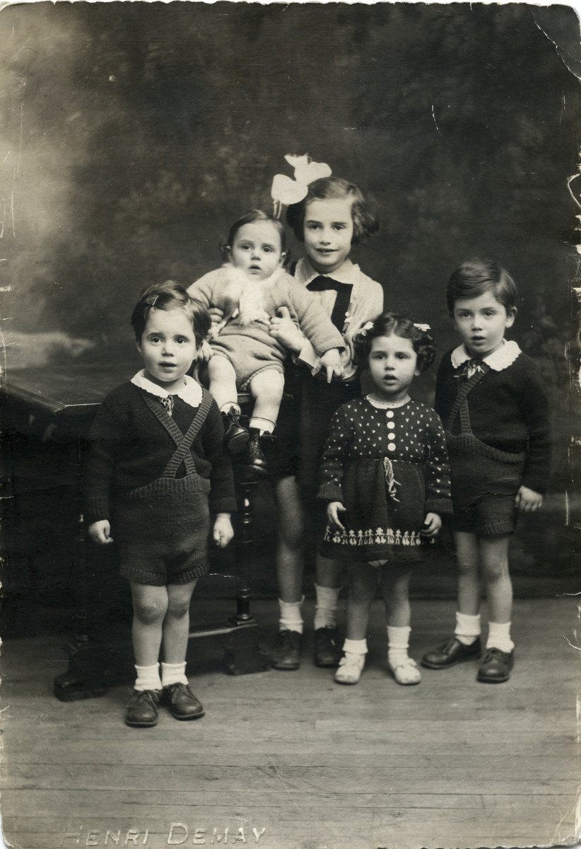 Studio portrait of the five Weisz siblings.  Pictured (left to right) are Georges, Yehudit holding brother Paul,  Esther, and Georges' twin Henri.