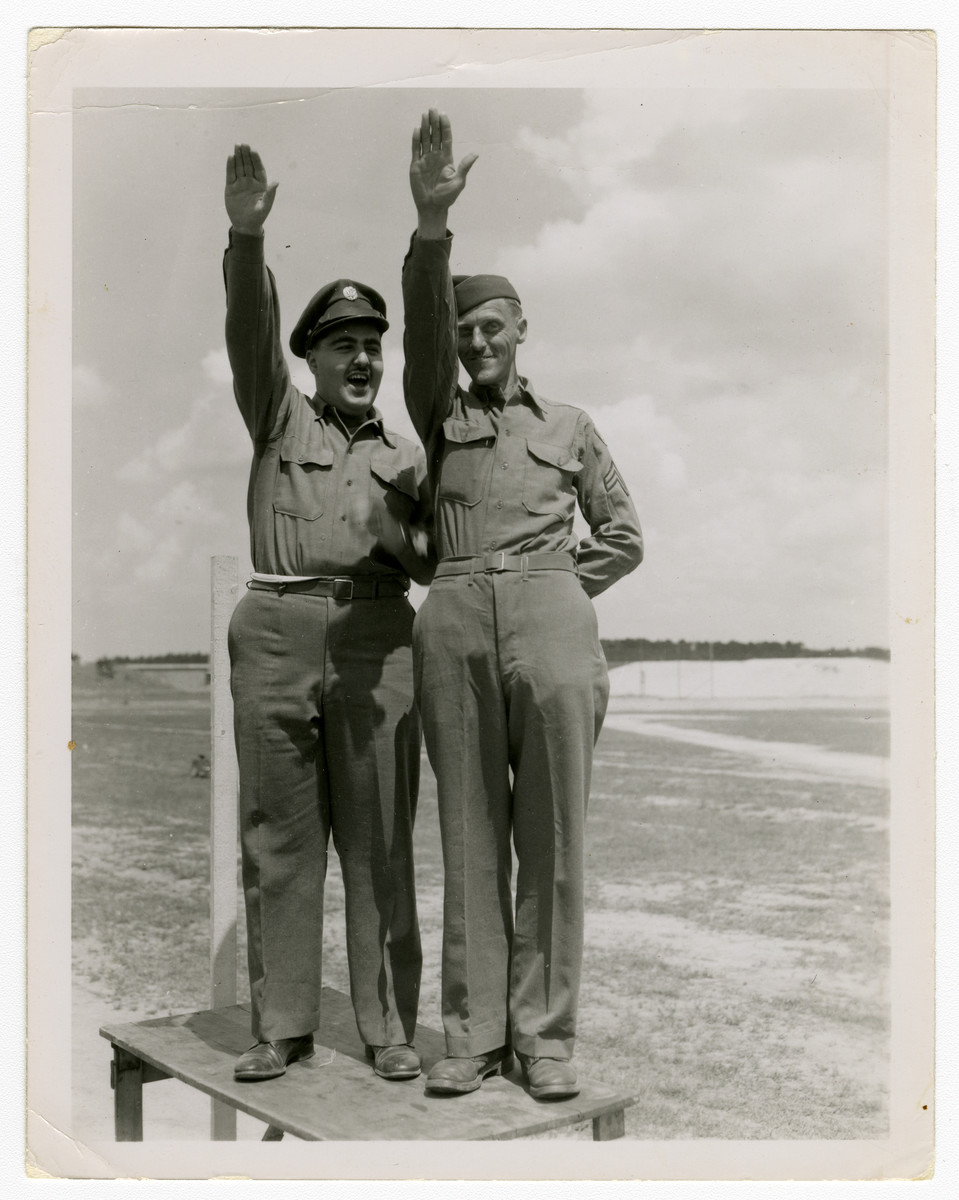 Two American soldiers jokingly give Nazi salutes.