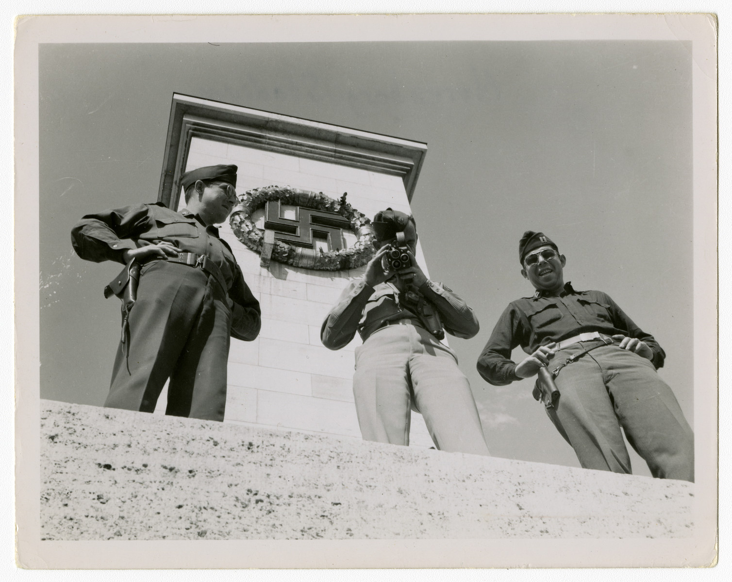 Three American soldiers, one with a camera, visit the Nazi stadium in Nuremberg.