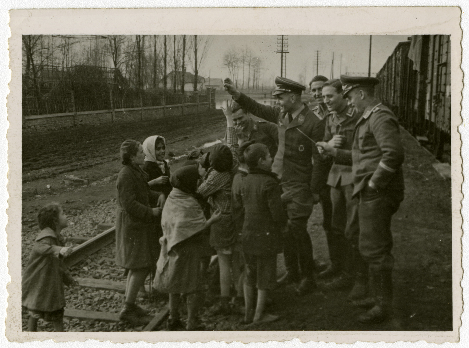 Members of the German Luftwaffe engage with local children by the tracks of an unidentified railway.  This image is one of twenty-six photographs and contained in an album found by Jacob Igra in an apartment in Sosnowiec after the war. Many of the photographs are believed to have been taken by a soldier with the SD-SIPO (Sicherheitspolizei) following the invasion of Poland in 1939. Additional photographs depict einsatzgruppen activities at sites throughout Nazi occupied Eastern Europe and may have been later additions to the album.