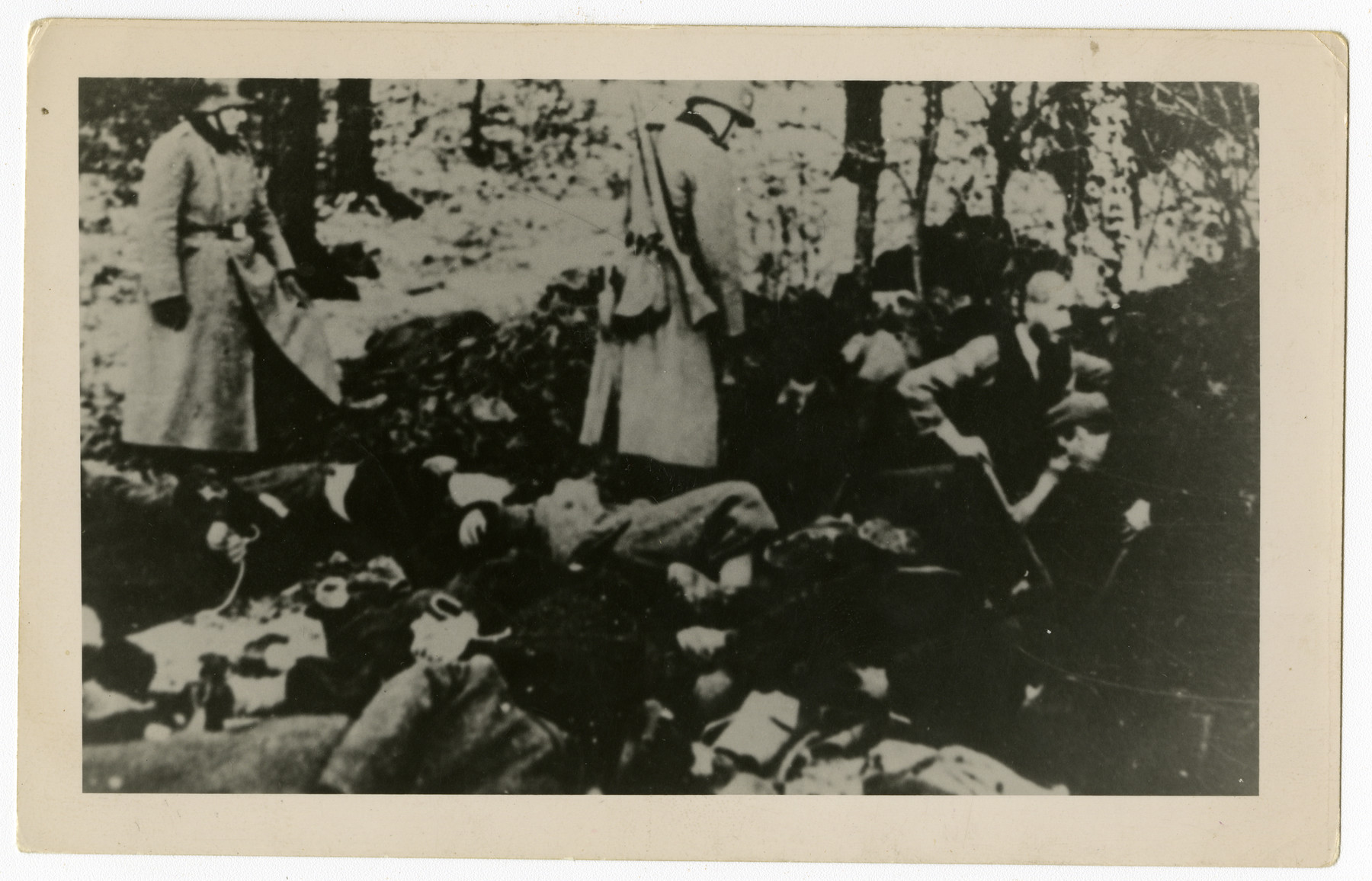Men with shovels dig pits next to the corpses of those recently executed by German police,  This copy print is one of twenty-six photographs contained in an album found by Jacob Igra in an apartment in Sosnowiec after the war. Many of the photographs are believed to have been taken by a soldier with the SD-SIPO (Sicherheitspolizei) following the invasion of Poland in 1939. Additional photographs depict einsatzgruppen activities at sites throughout Nazi occupied Eastern Europe and are likely later additions to the album.