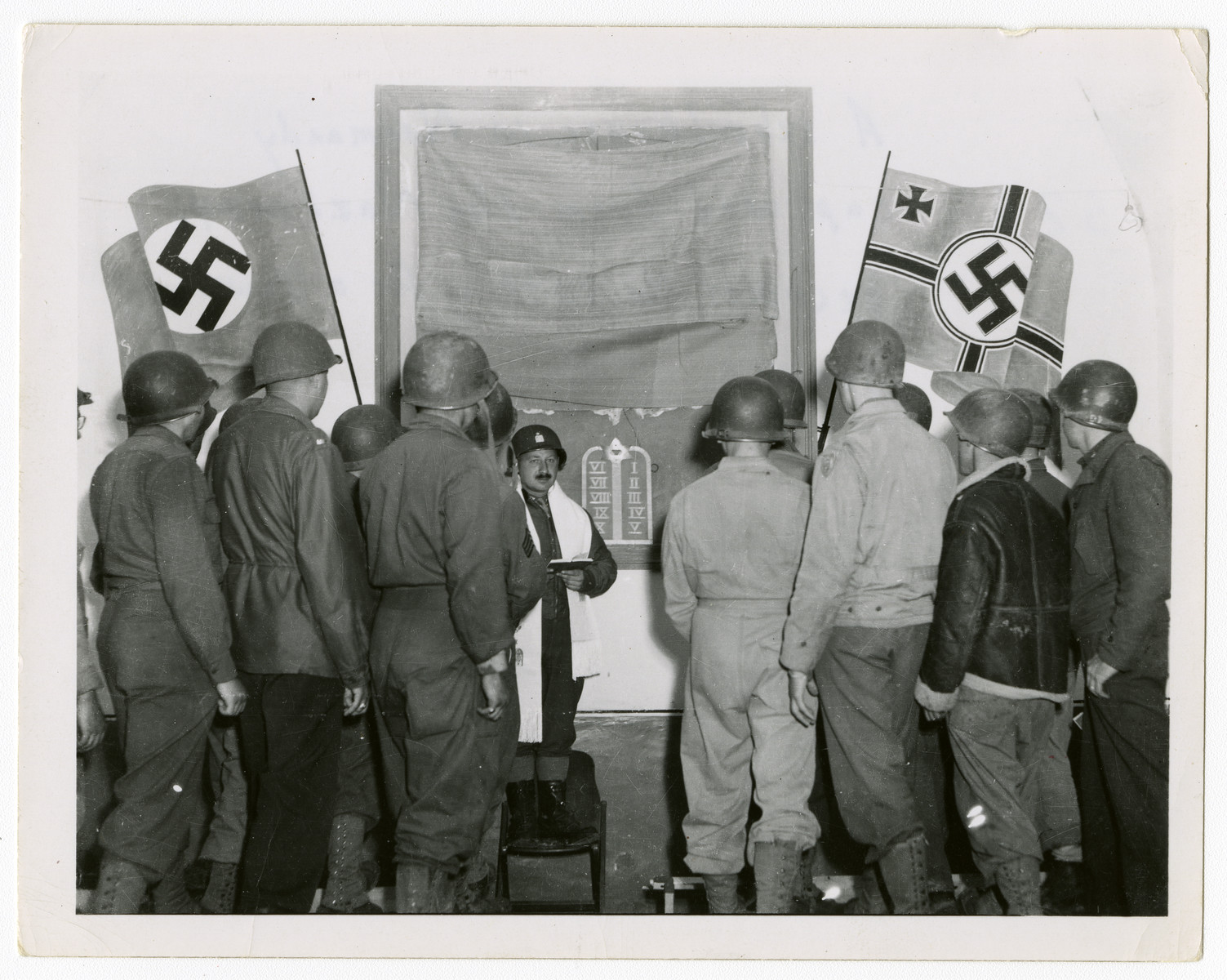 """Jewish soldiers gather for a prayer service in a room still bedecked with Nazi flags.  Original caption reads, """"A schoolhouse in Normandy captured from the Nazi army becomes the setting for a Jewish Service."""""""