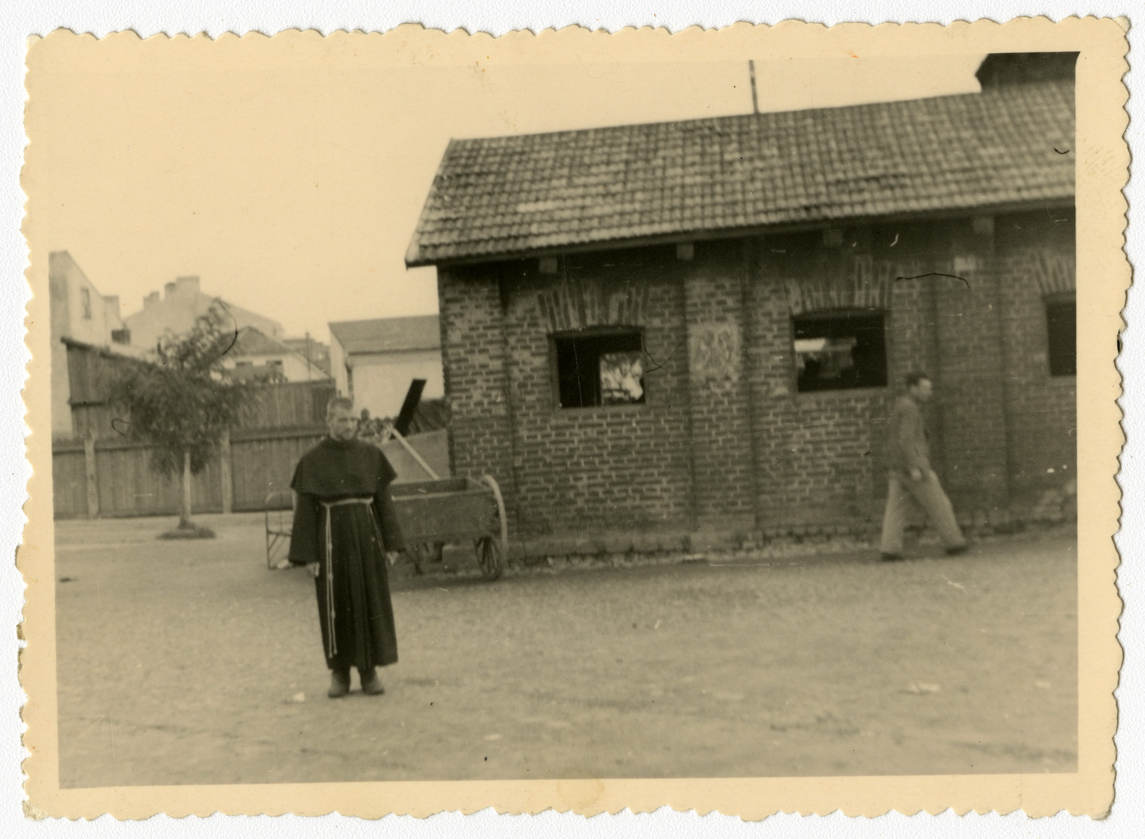 A Polish cleric stands in an open square.  This image is one of twenty-six photographs contained in an album found by Jacob Igra in an apartment in Sosnowiec after the war. Many of the photographs are believed to have been taken by a soldier with the SD-SIPO (Sicherheitspolizei) following the invasion of Poland in 1939. Additional photographs depict einsatzgruppen activities at sites throughout Nazi occupied Eastern Europe and may have been later additions to the album.