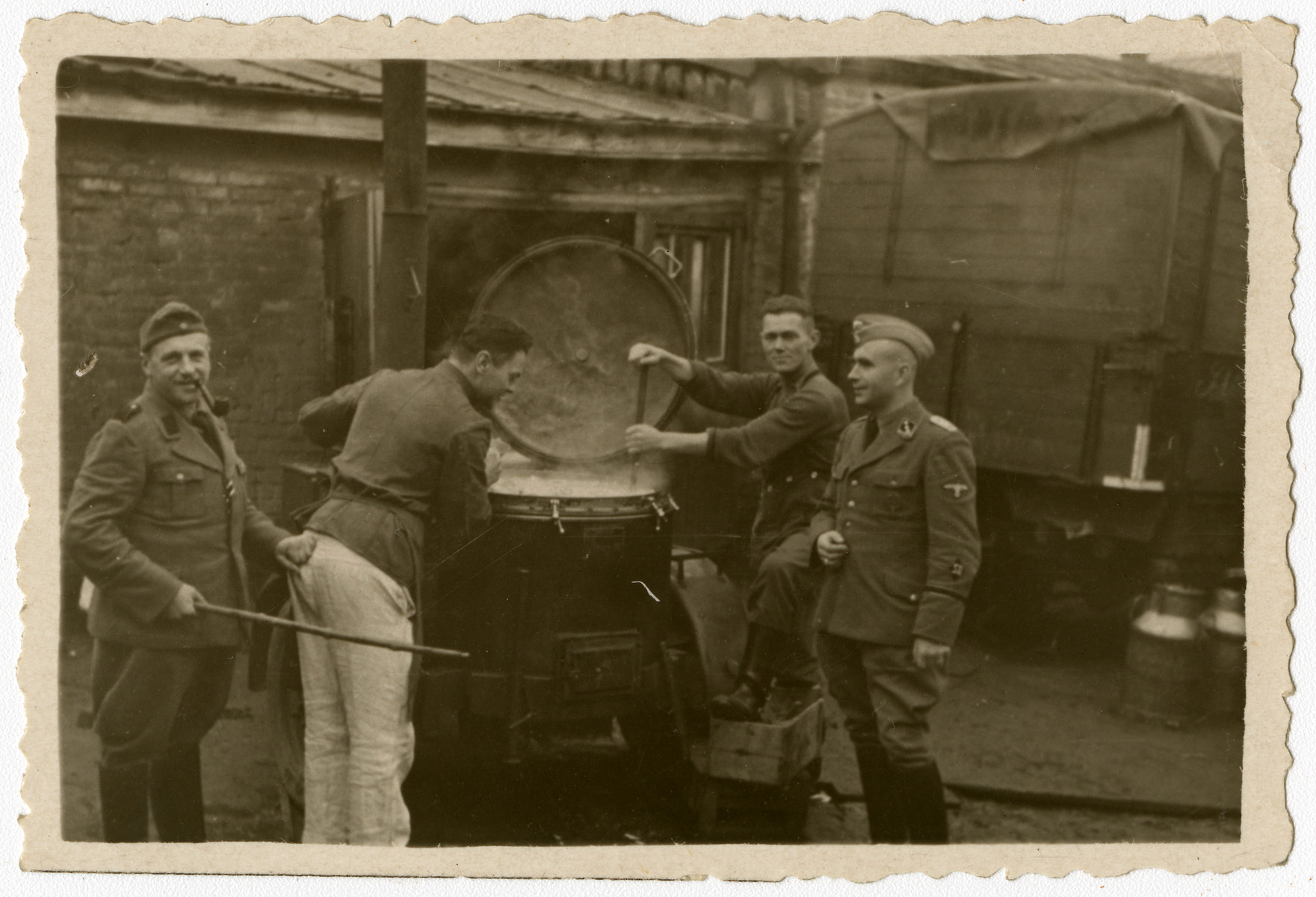 SD personnel pose as they prepare food in a mobile field kitchen.    This image is one of twenty-six contained in an album found by Jacob Igra in an apartment in Sosnowiec after the war. Many of the photographs are believed to have been taken by a soldier with the SD-SIPO (Sicherheitspolizei) following the invasion of Poland in 1939. Additional photographs depict einsatzgruppen activities at sites throughout Nazi occupied Eastern Europe and may have been later additions to the album.