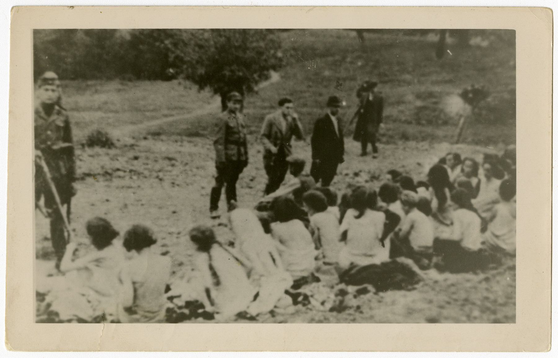 German police and auxiliaries in civilian clothes look on as a group of Jewish women are forced to undress before their execution.  This copy print of a wideley circulated image (see WS# 43195) is one of twenty-six  photographs and copy prints contained in an album found by Jacob Igra in an apartment in Sosnowiec after the war. Many of the photographs are believed to have been taken by a soldier with the SD-SIPO (Sicherheitspolizei) following the invasion of Poland in 1939. Additional photographs depict einsatzgruppen activities at sites throughout Nazi occupied Eastern Europe and may have been later additions to the album.