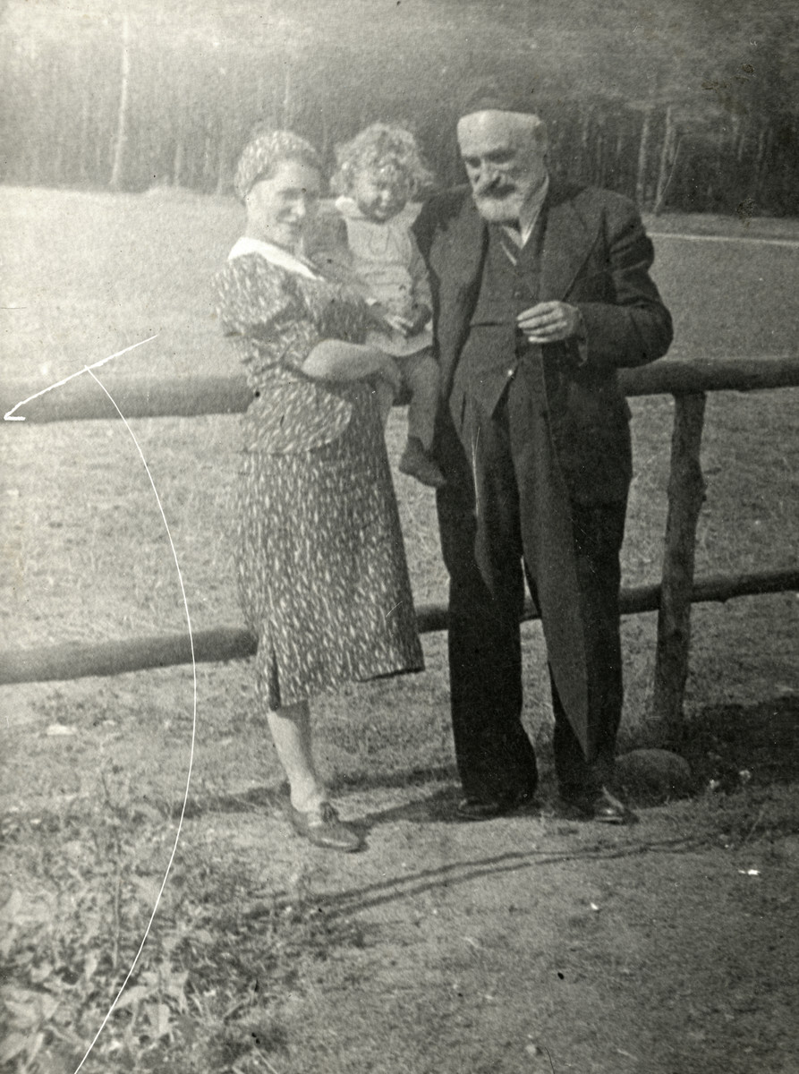 A Jewish family in Poland poses next to a wooden fence.   Pictured are Anka Blass holding her young son Rysio, and her father Ber Charney.