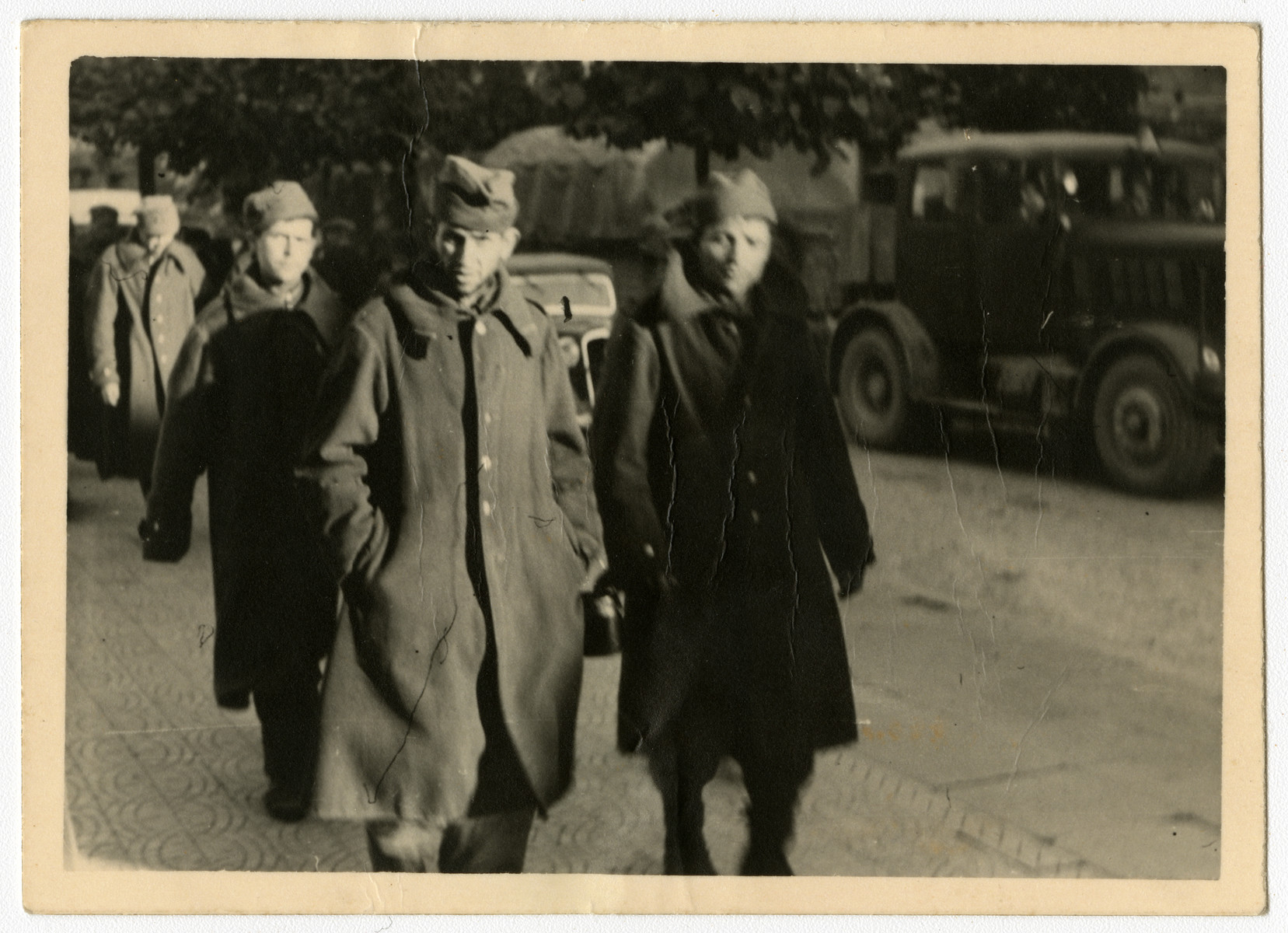 Polish soldiers, likely prisoners of war, walk in the middle of a city street.    This image is one of twenty-six contained in an album found by Jacob Igra in an apartment in Sosnowiec after the war. Many of the photographs are believed to have been taken by a soldier with the SD-SIPO (Sicherheitspolizei) following the invasion of Poland in 1939. Additional photographs depict einsatzgruppen activities at sites throughout Nazi occupied Eastern Europe and may have been later additions to the album.