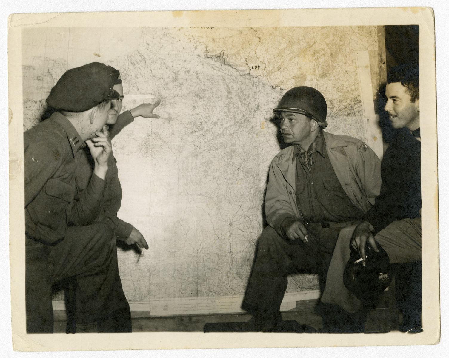 """Edward G. Robinson visits American military headquarters in Normandy.  The original captions read: """"Edward G. Robinson: What is the next target?"""" and, """"Edward G. Robinson visits Normandy."""""""