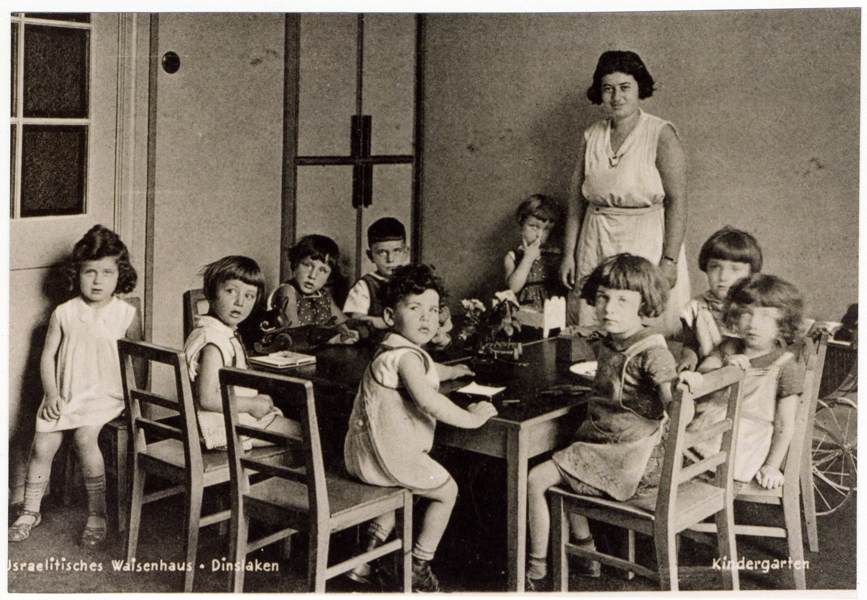 Younger children sit around a table in the Dinslaken children's home.  Hans Frank (the only boy in the photograph) is seated in the back, left corner of the table.