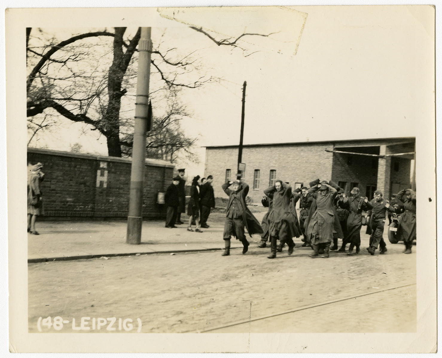 Captured German troops march down a street in Leipzig with their hands on their heads.