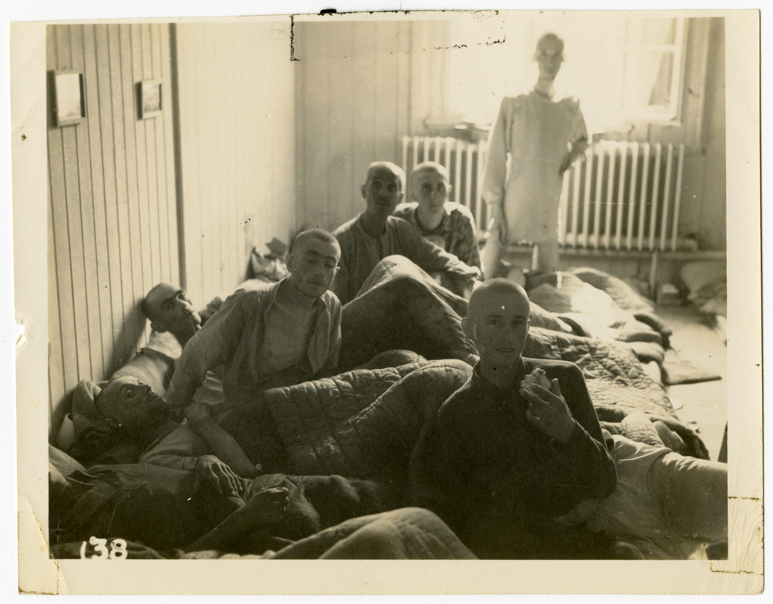 Survivors of the Buchenwald concentration camp recuperate inside a building [perhaps a makeshift hospital] following liberation.